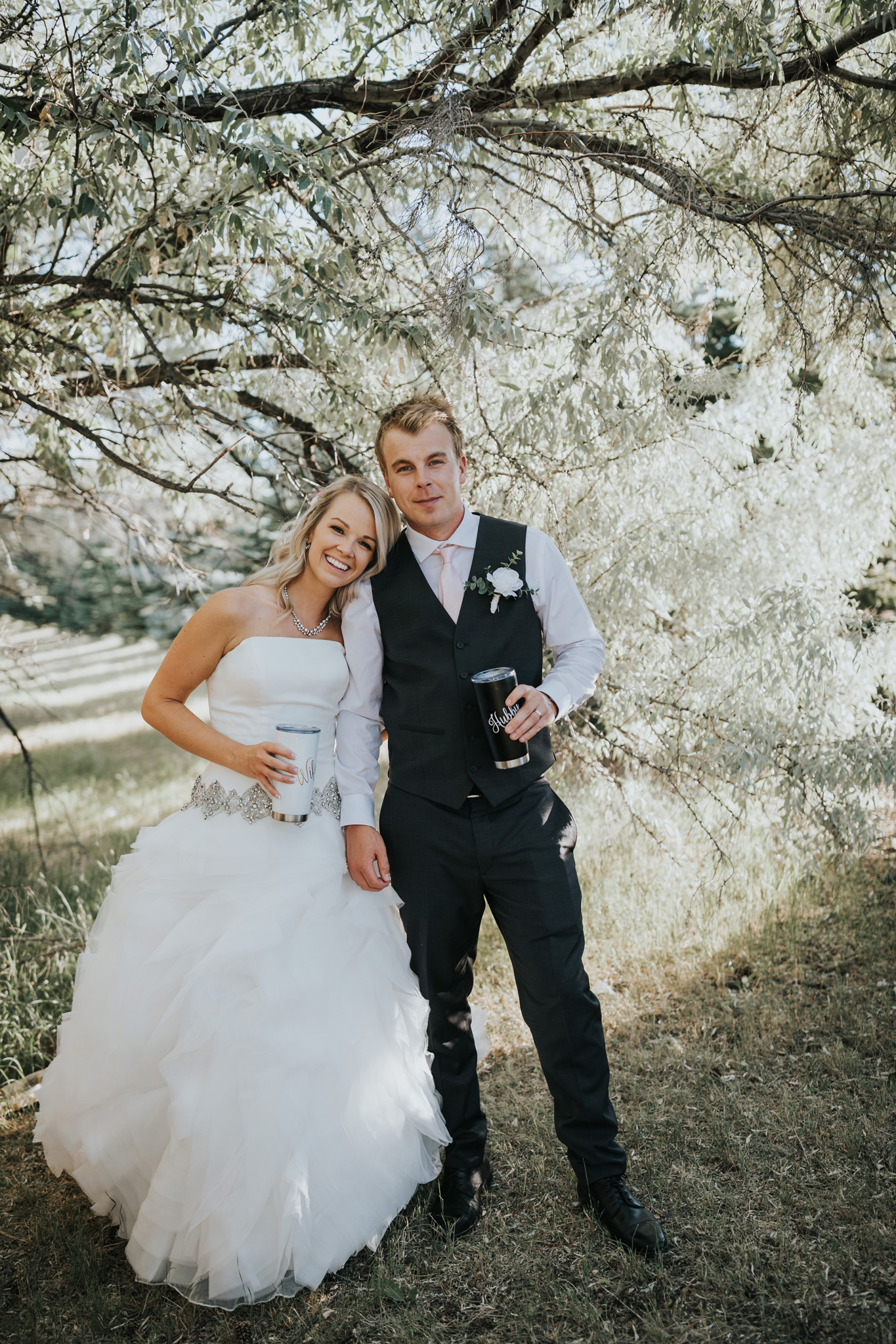 bride and groom stand cuddling holding matching travel mugs