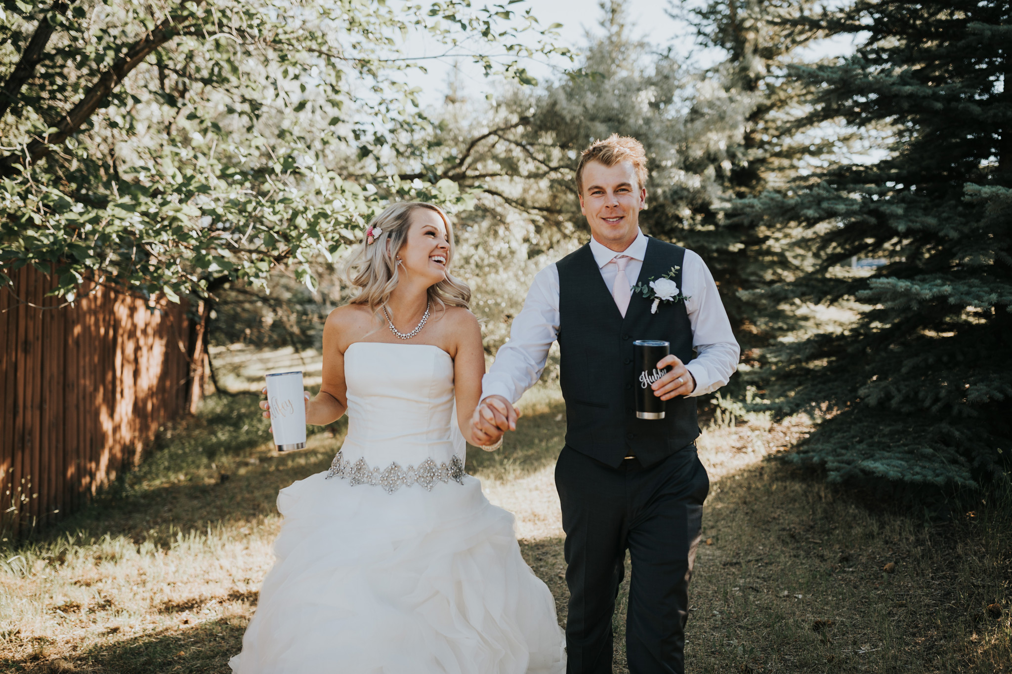 bride and groom walking laughing holding matching wifey hubby travel mugs
