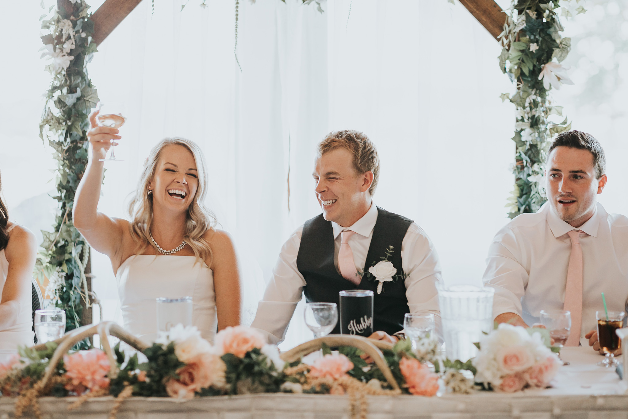 bride holds up her glass laughing at reception head table