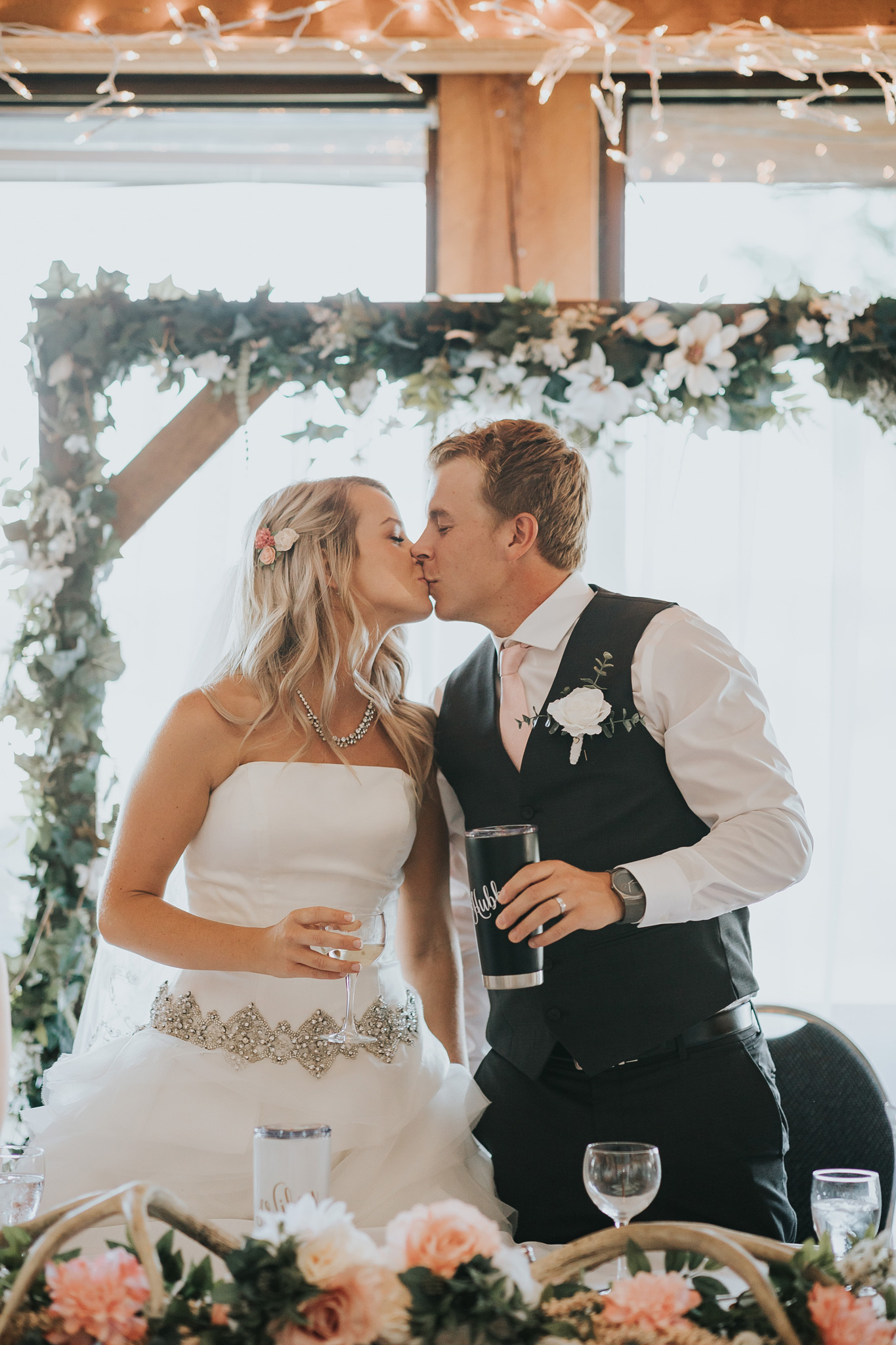 bride and groom kiss at reception head table