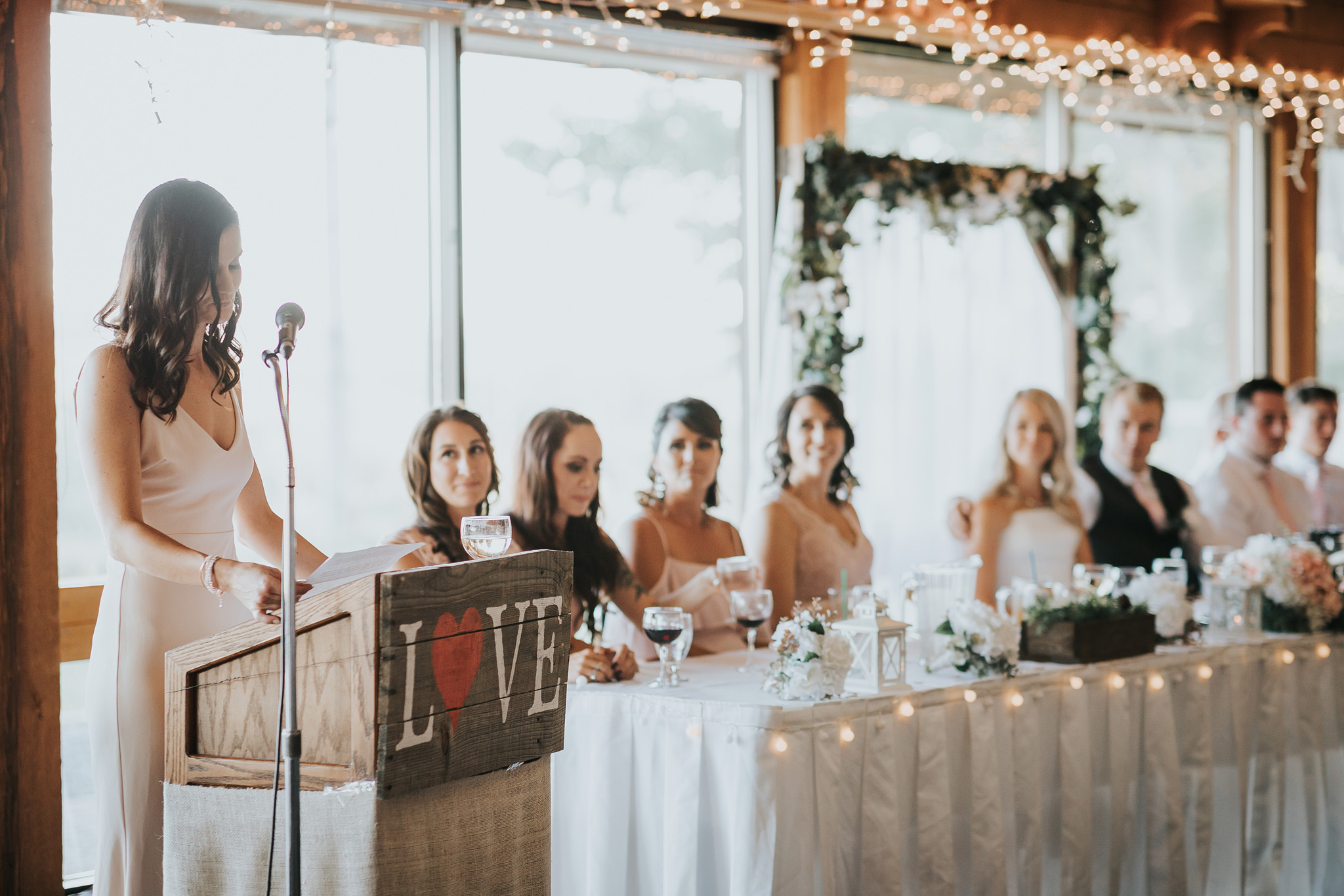 bridal party watches as maid of honour makes her speech