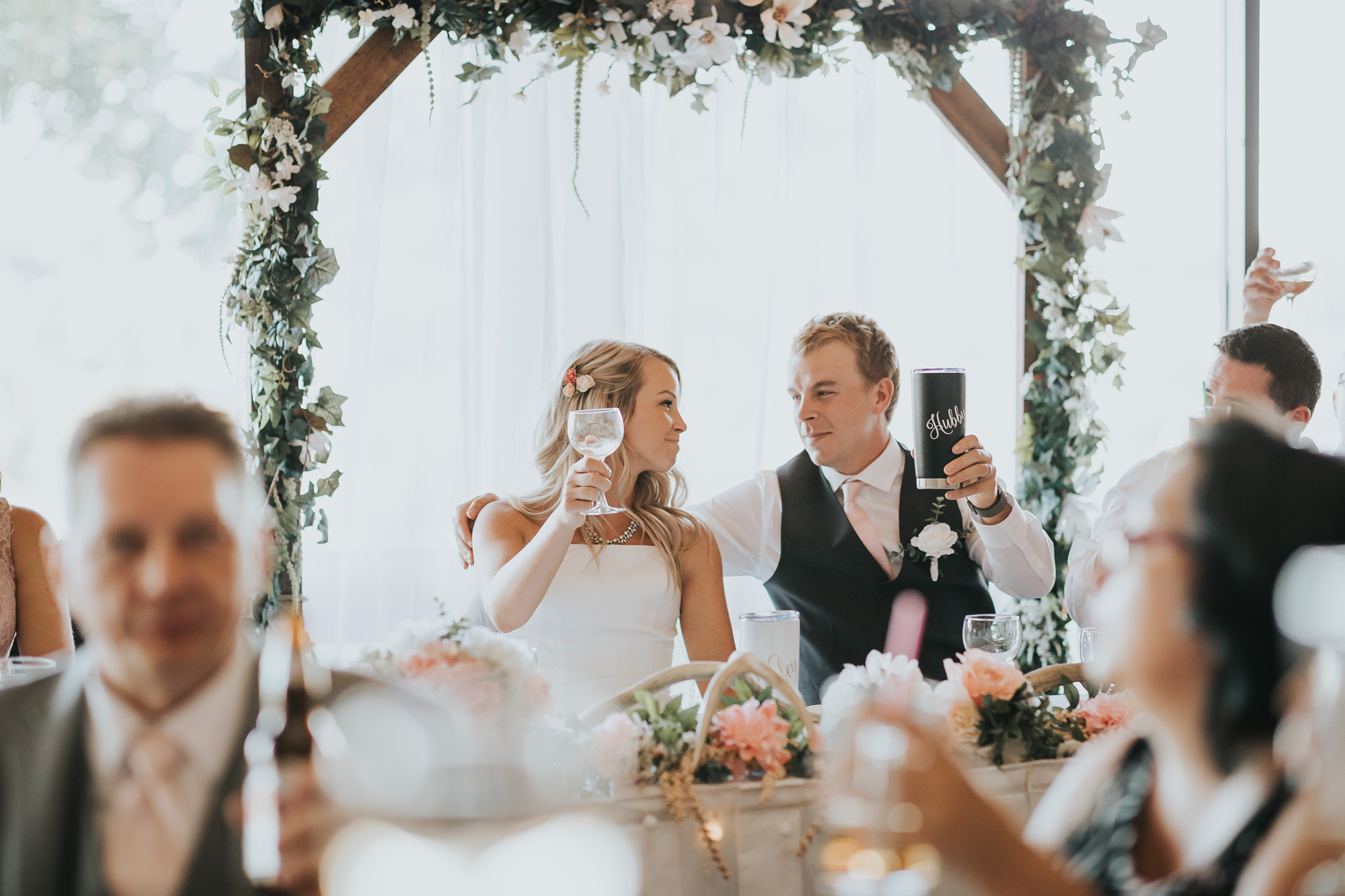 bride and groom hold up their glasses for a toast