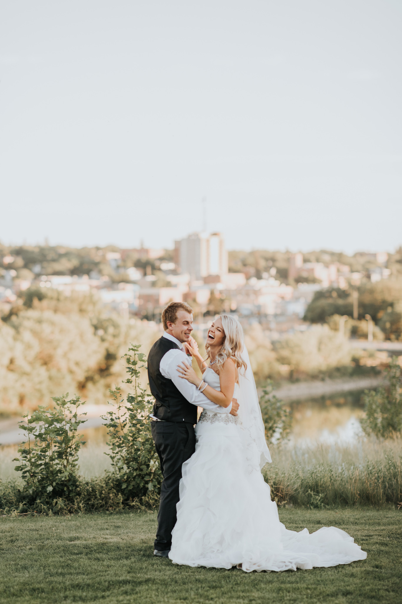 just married couple dancing and laughing view of city skyline medicine hat alberta