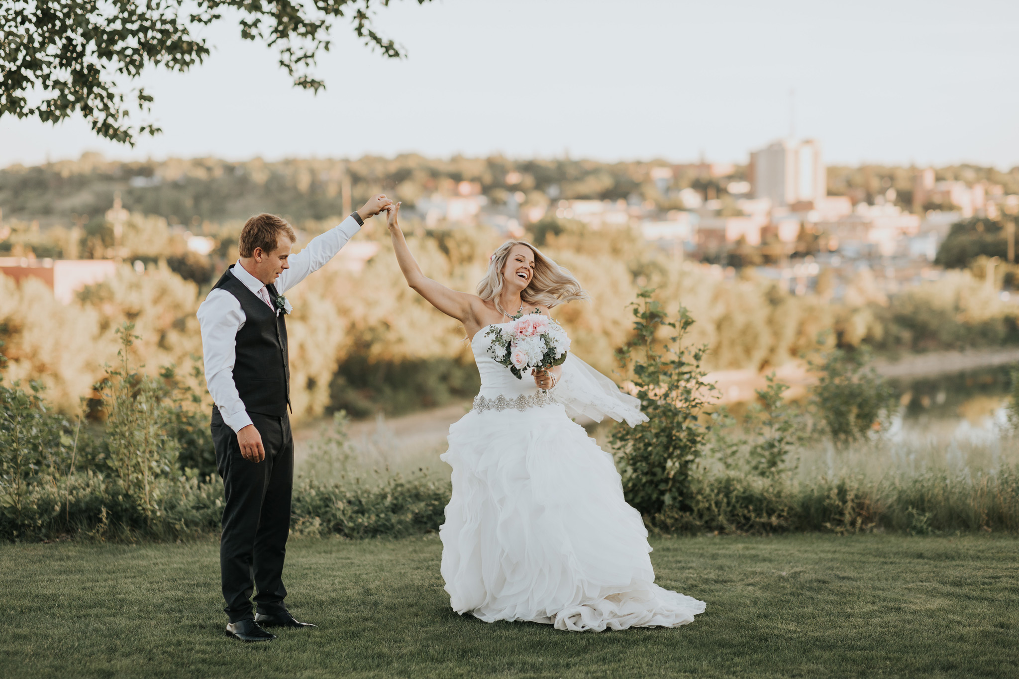 groom spins bride dancing over city skyline medicine hat alberta