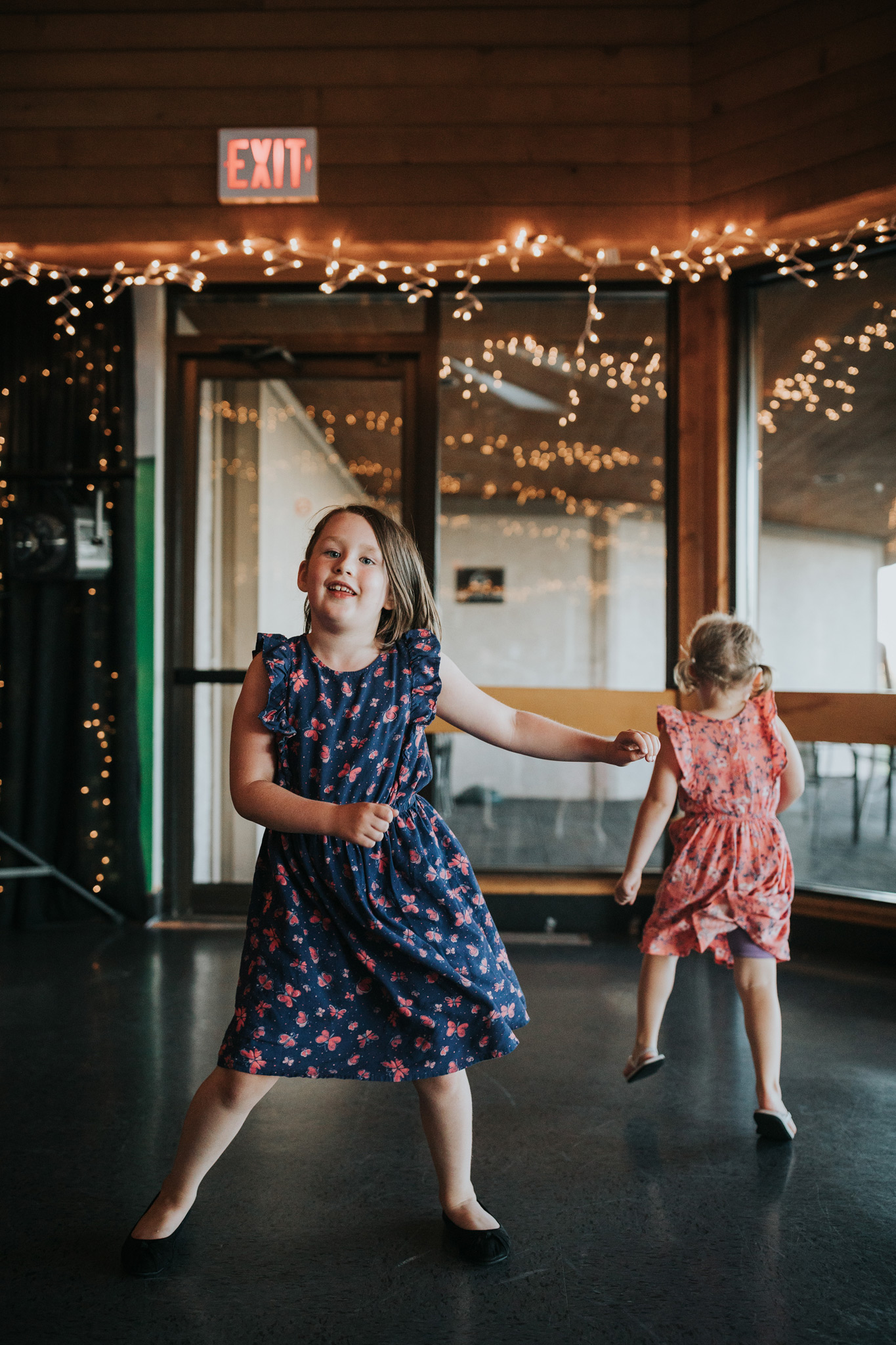 two young girls dancing at the wedding reception