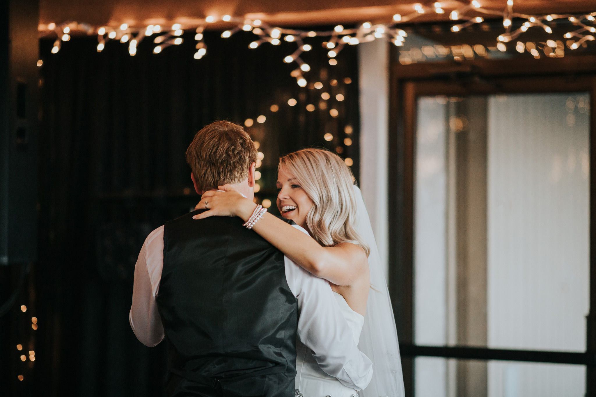 bride smiling at groom during first dance