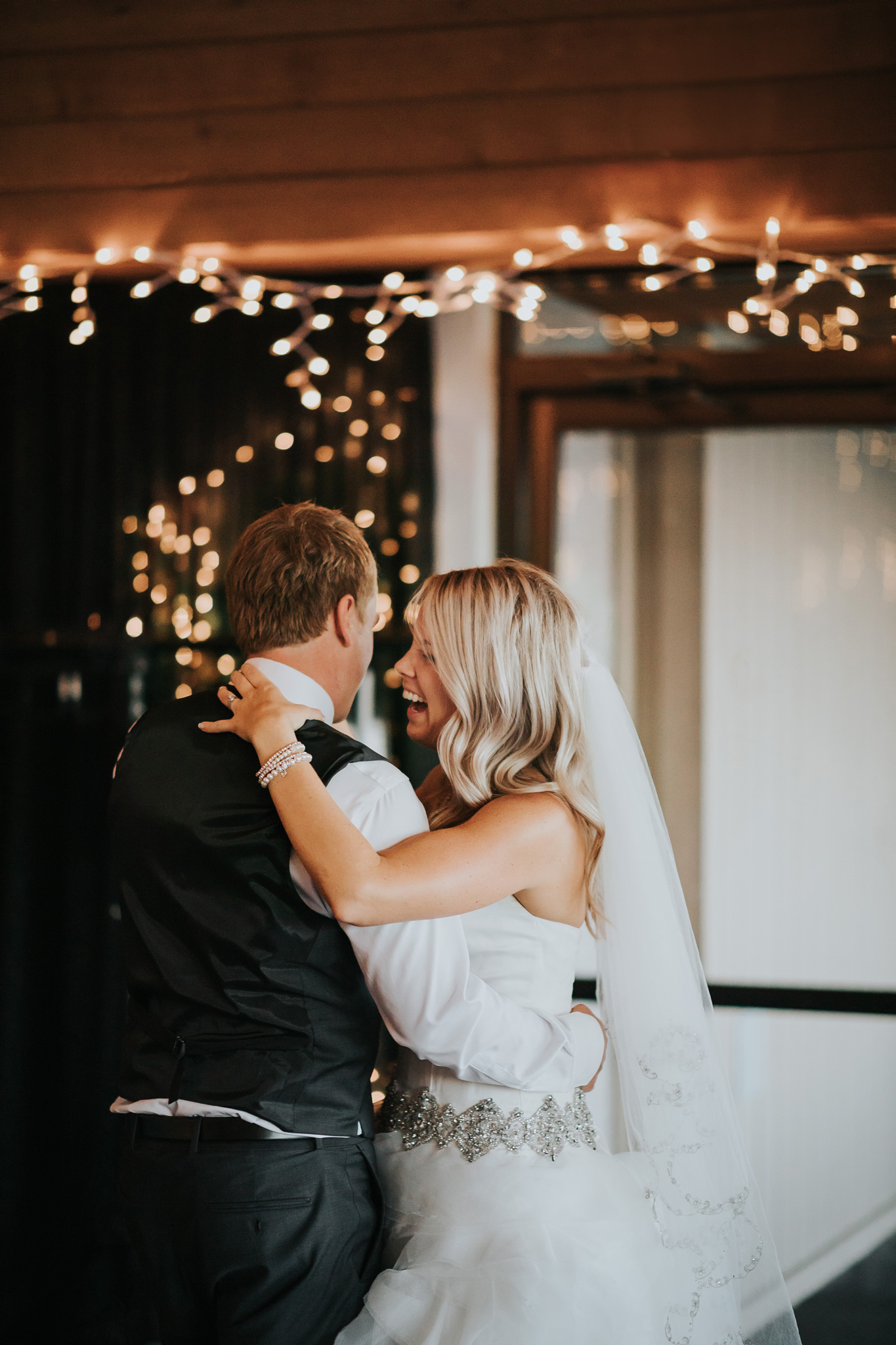 bride laughing with groom during first dance