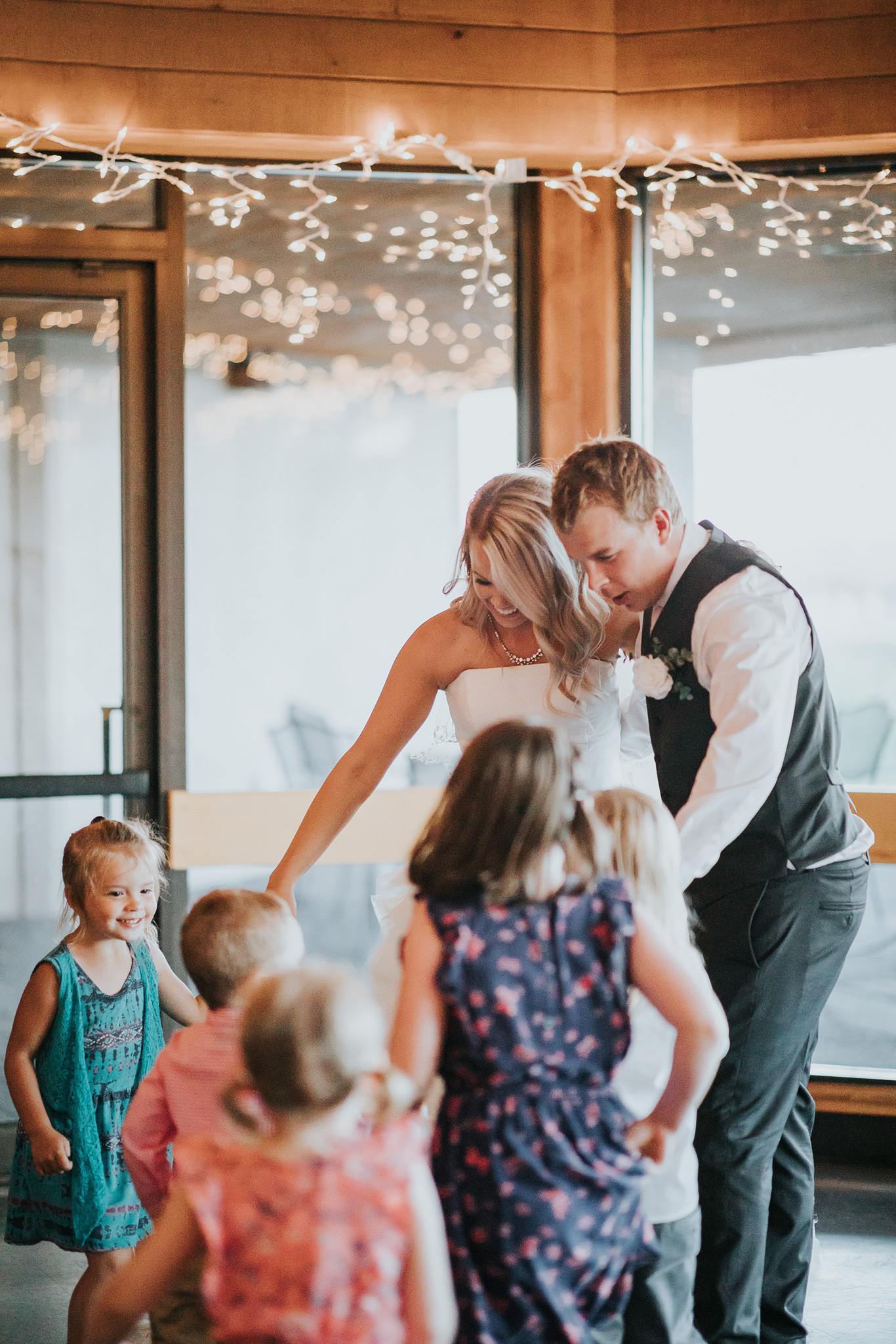 a group of kids join in bride and grooms first dance