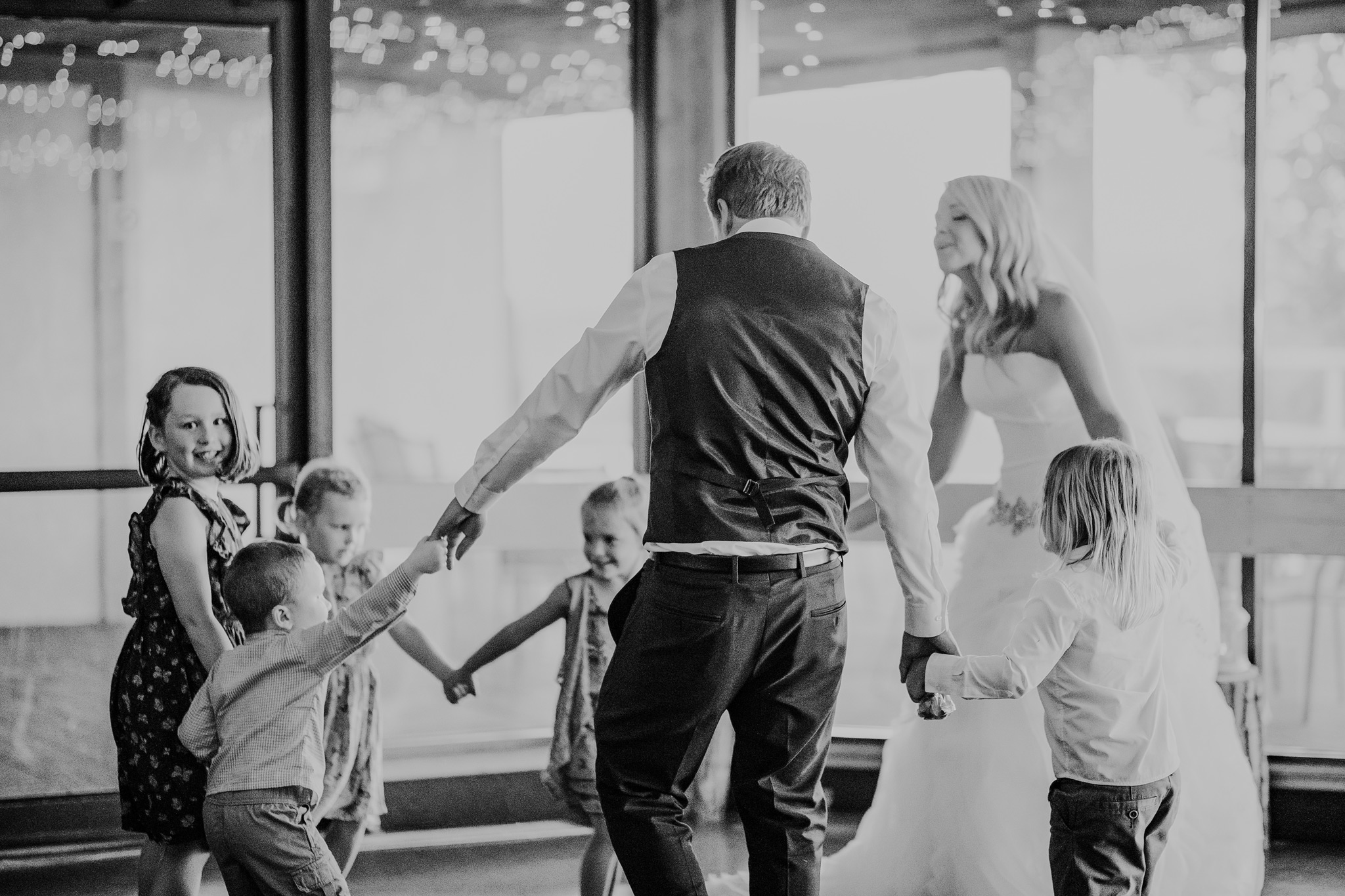 bride and groom dancing with kids during their first dance