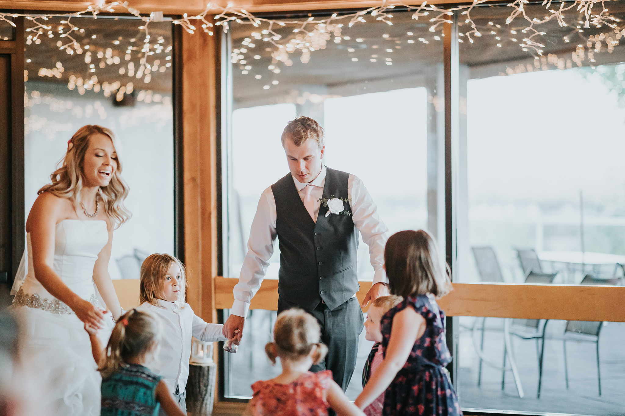 bride and groom dancing in a circle with kids during first dance