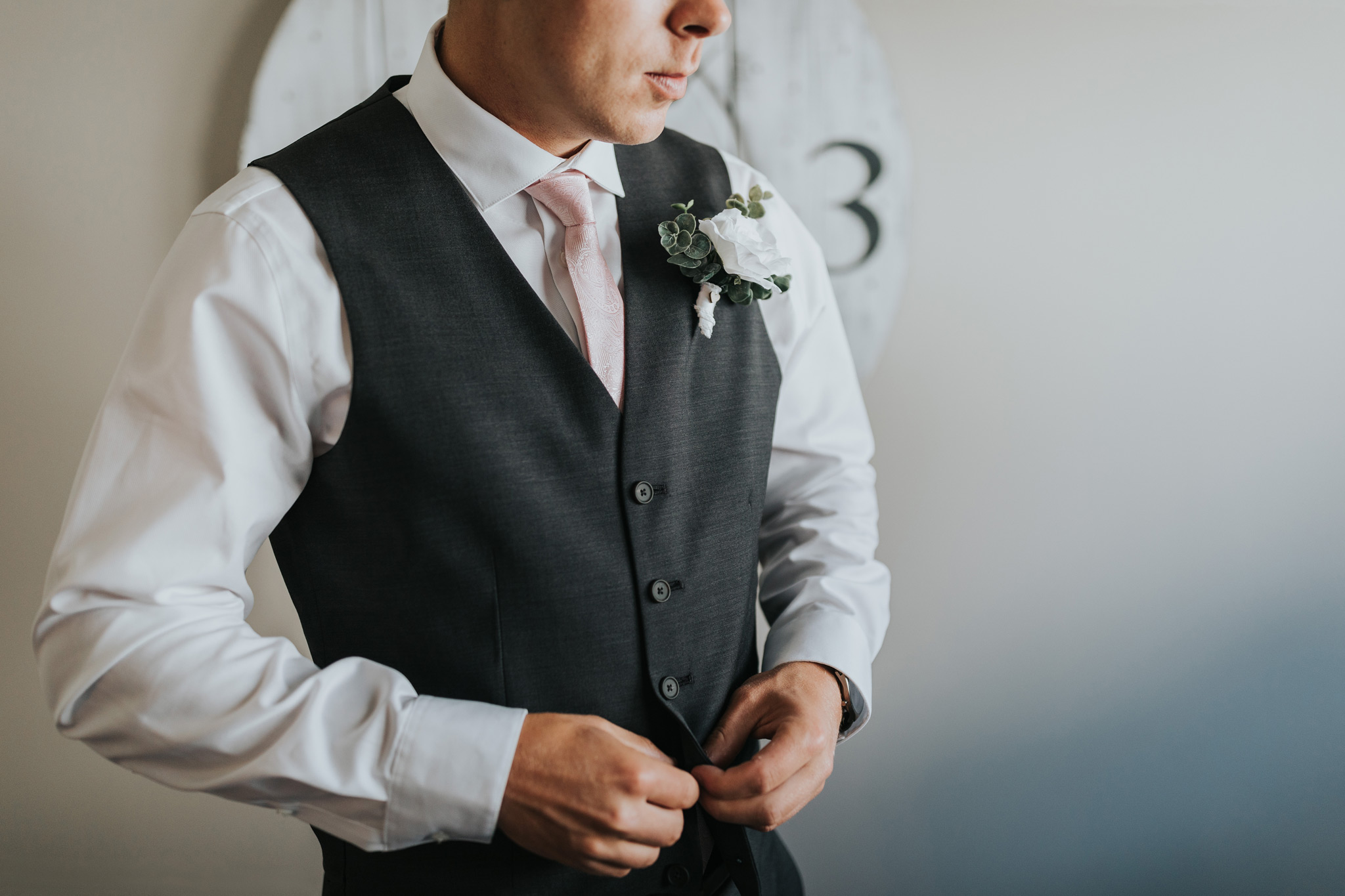 groom doing up his buttons getting ready photo