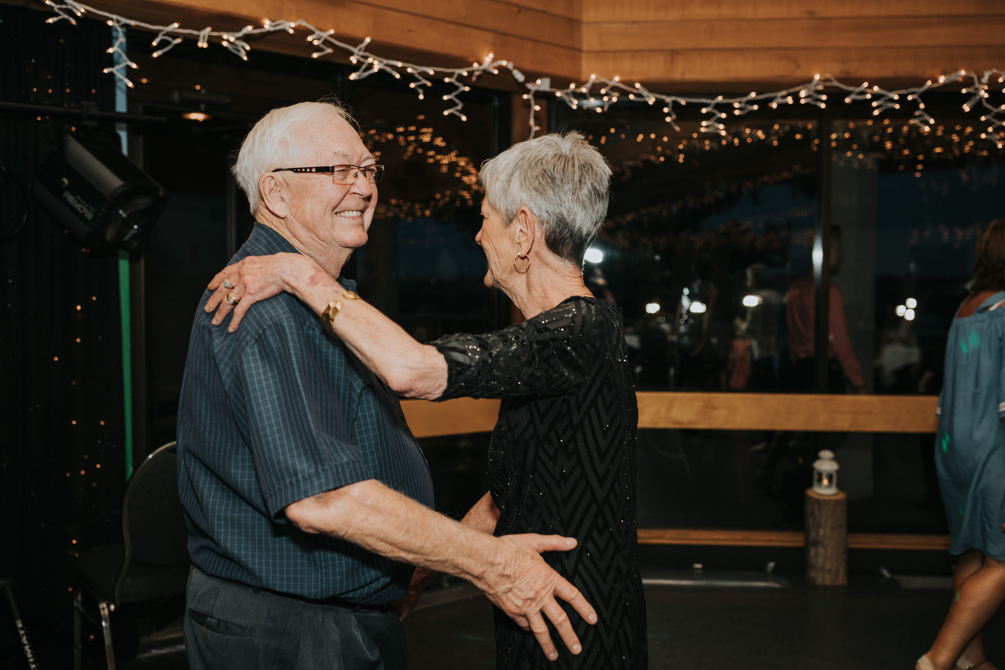 elderly couple dancing smiling at wedding reception