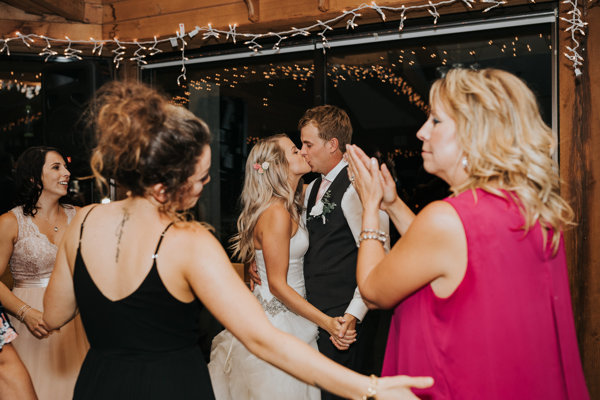 bride and groom kiss on the dance floor with guests around them