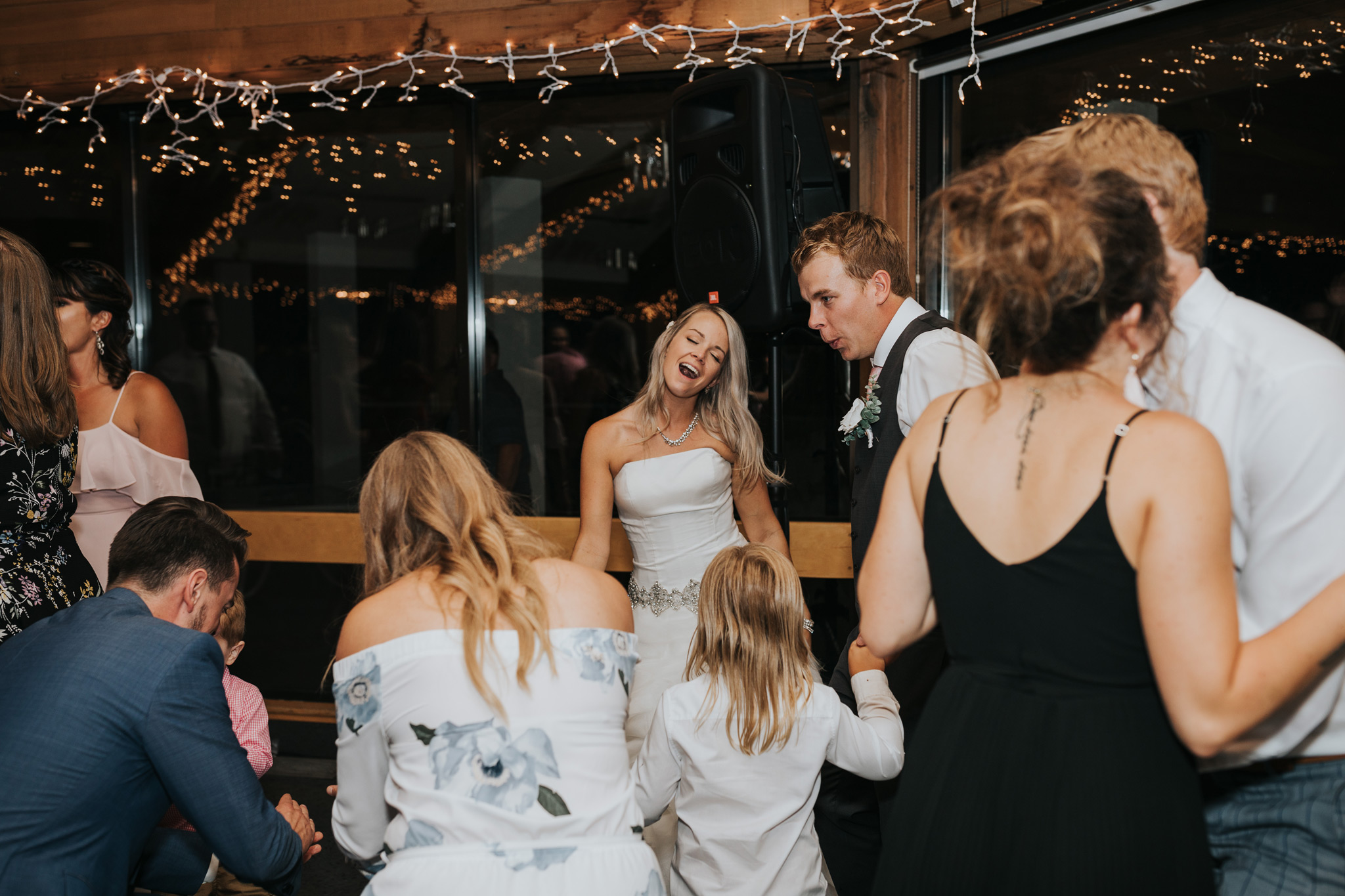 dance floor at wedding reception filled with guests and bride and groom