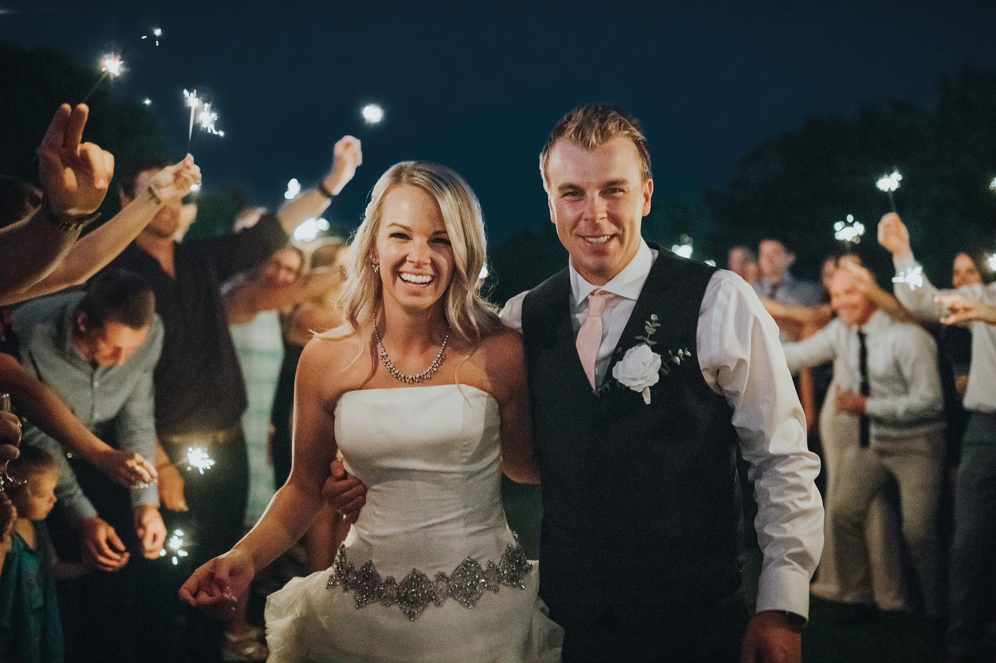 bride and groom smile walking down sparkler exit