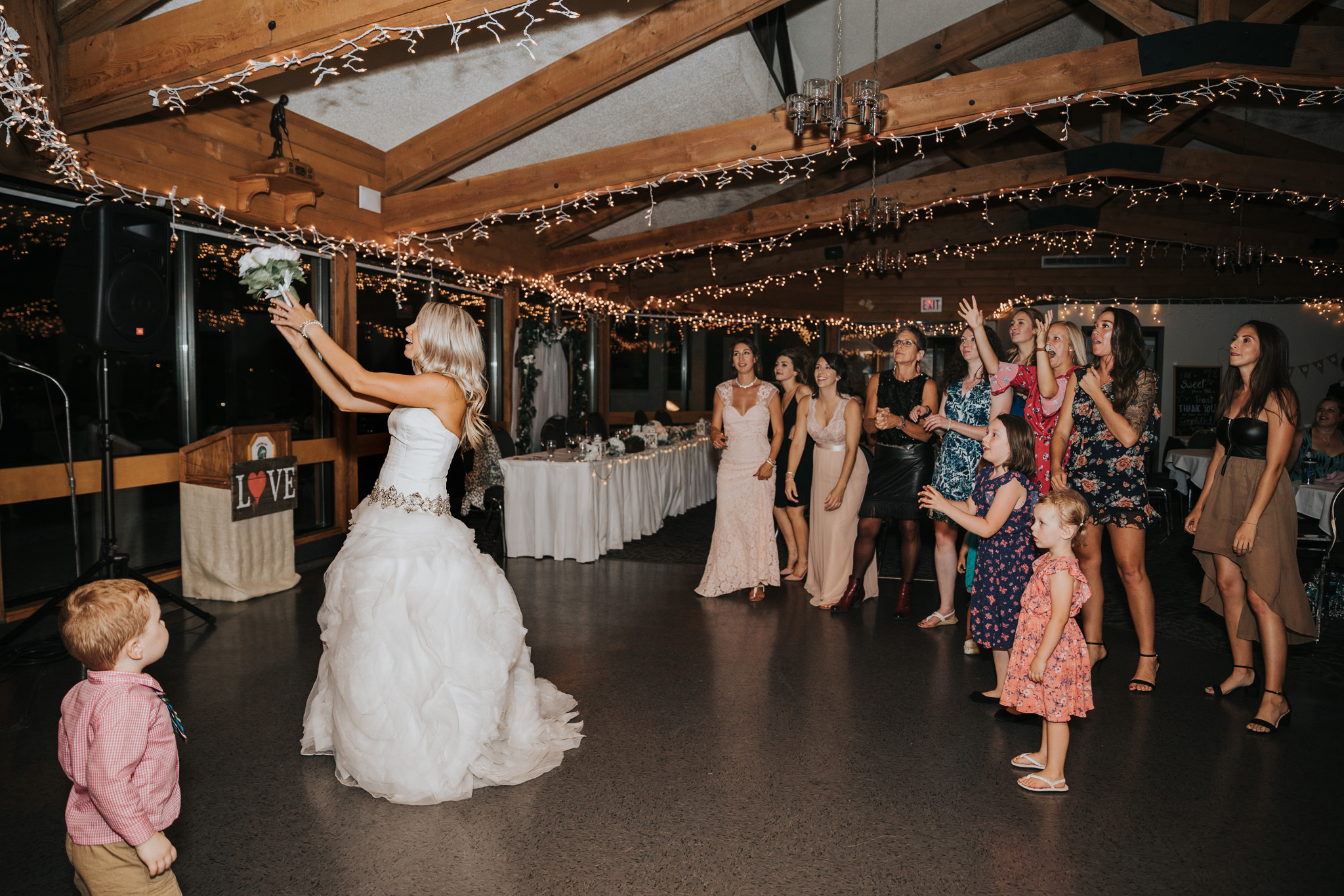 bride tossing her wedding bouquet at reception