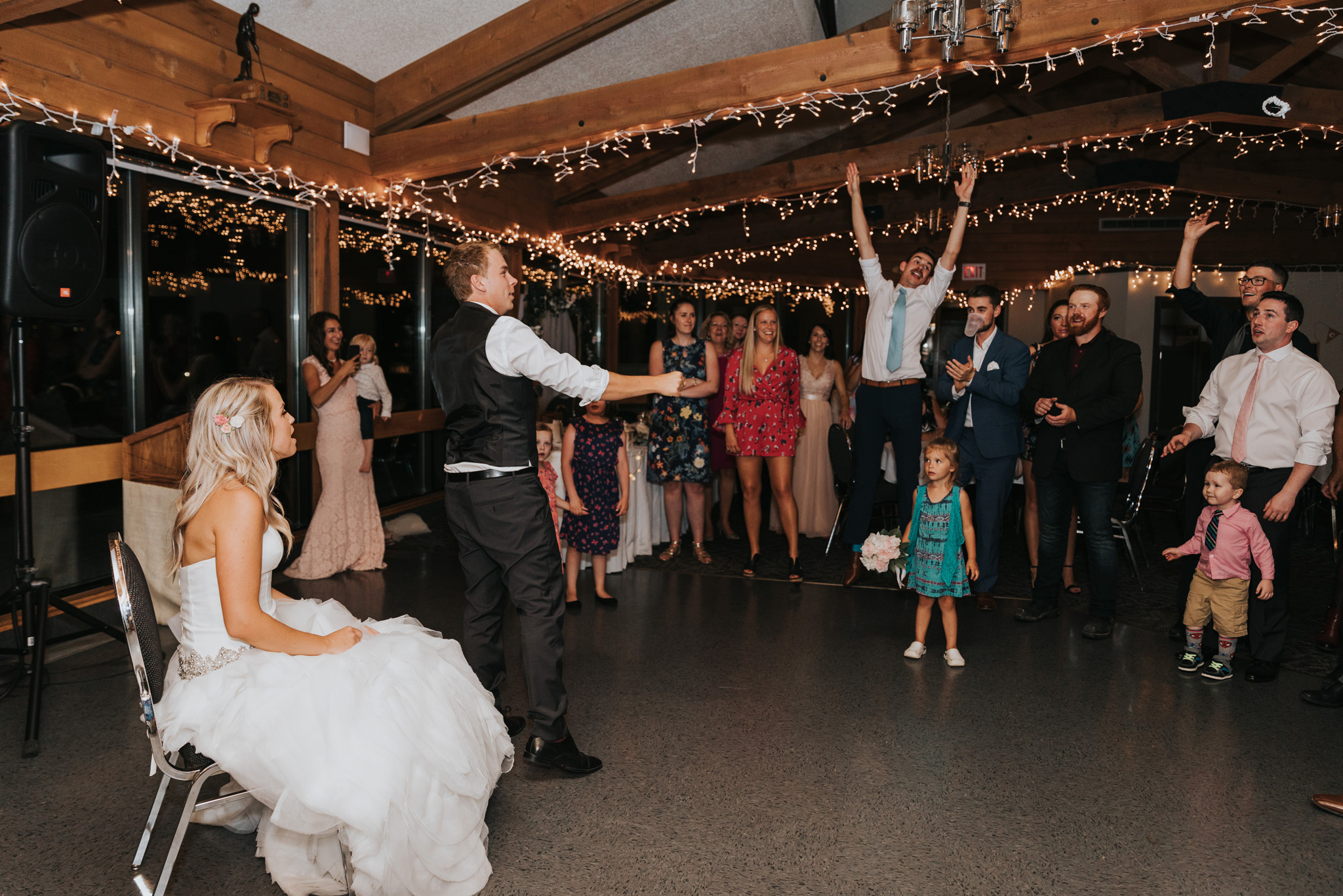 groom tosses garter at wedding reception