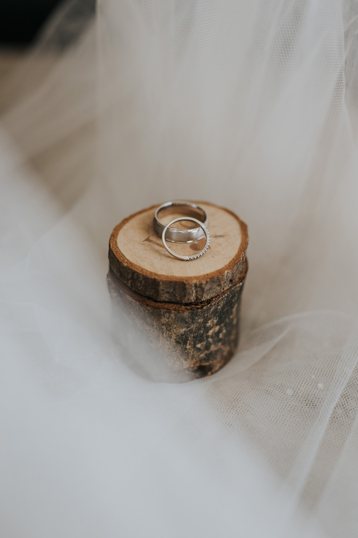 wedding rings placed on wooden ring box detail photo with veil