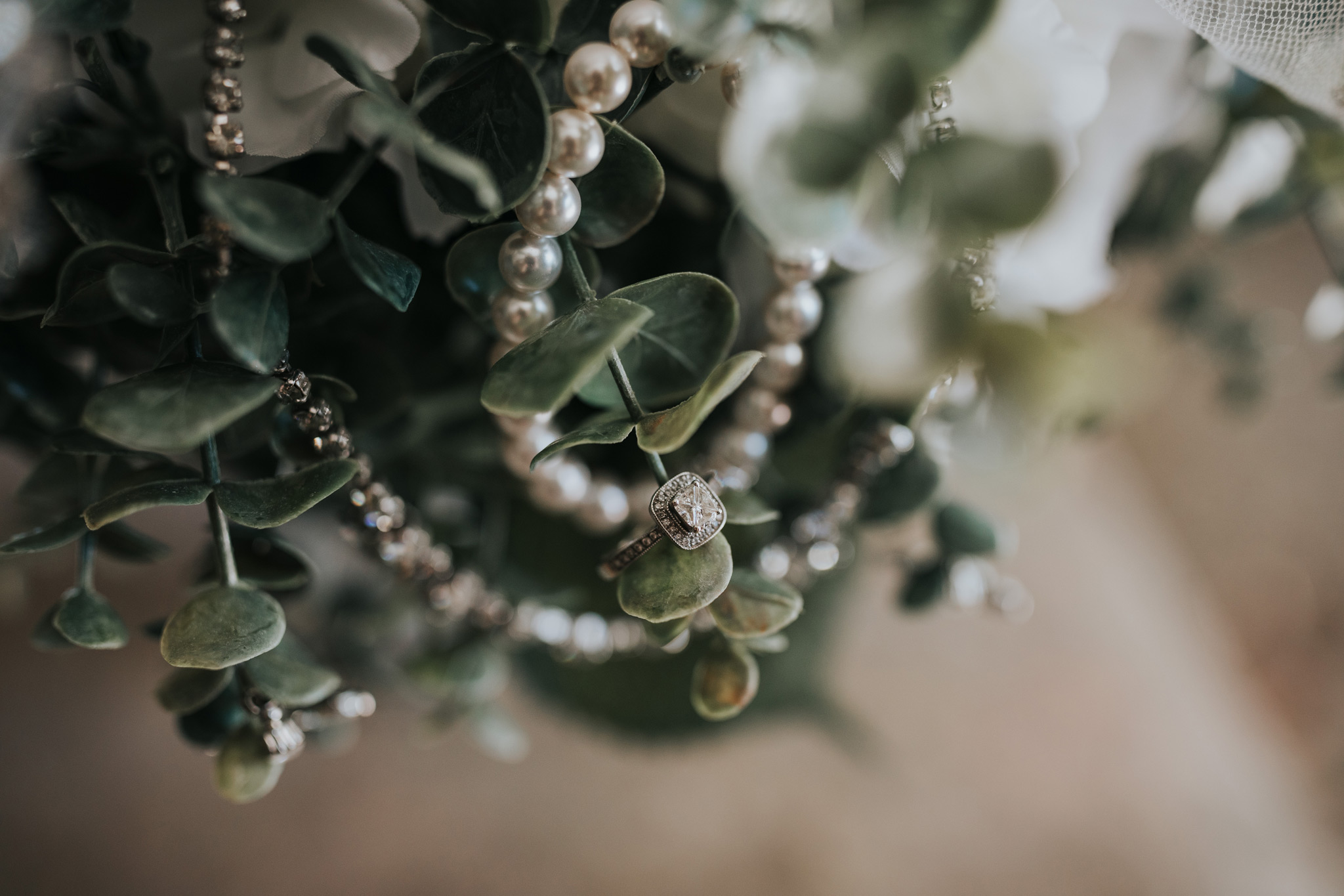 brides jewelry hanging in wedding bouquet greenery