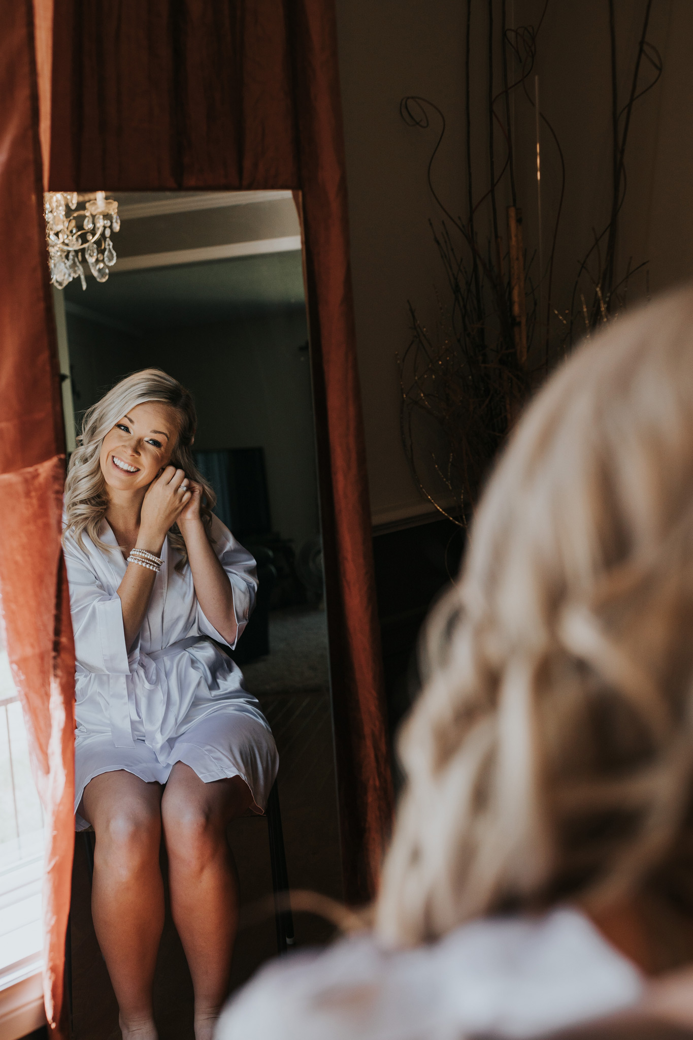 bride smiling in mirror putting on wedding jewelry