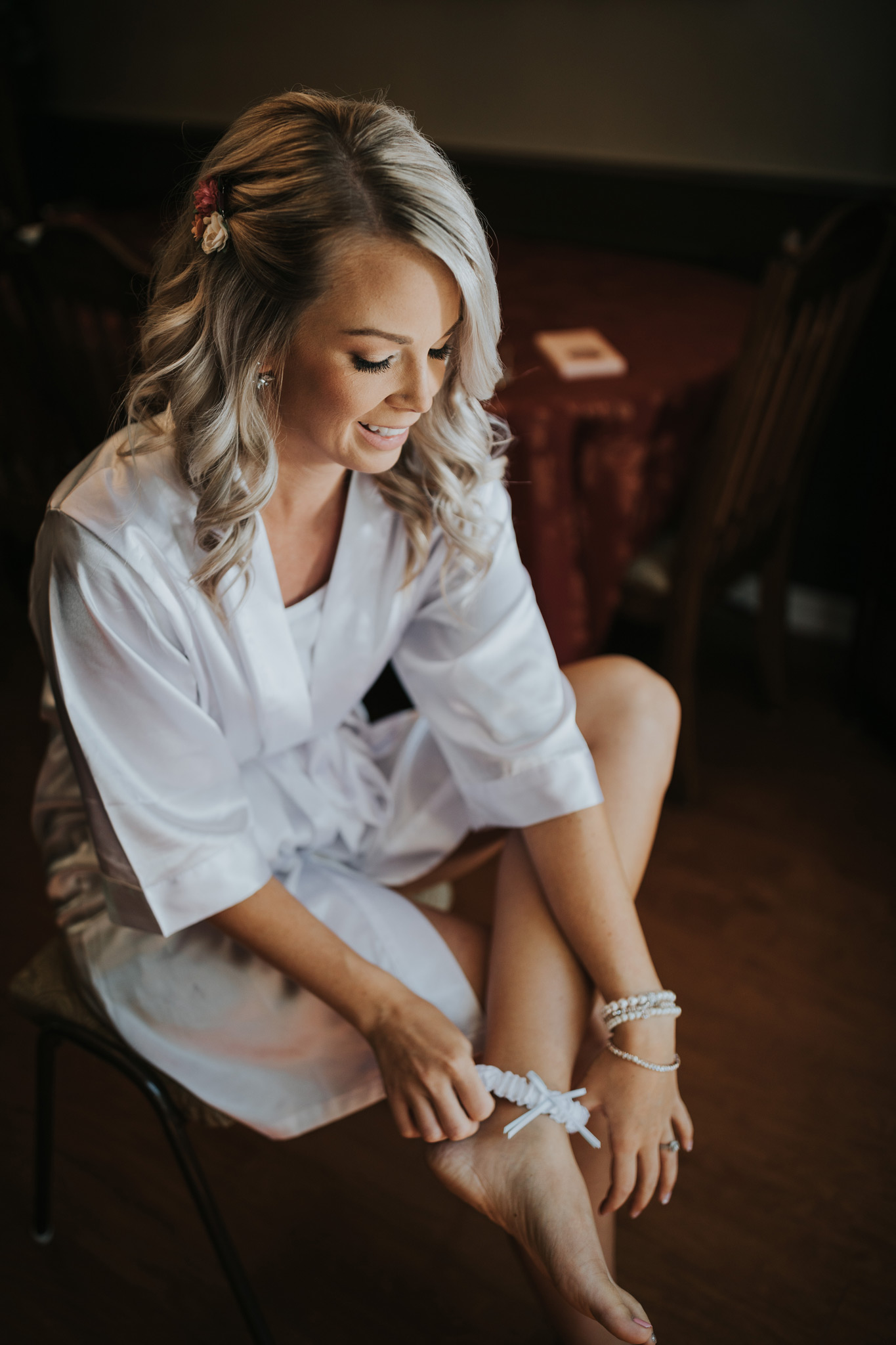 bride in robe putting on her garter medicine hat wedding photo