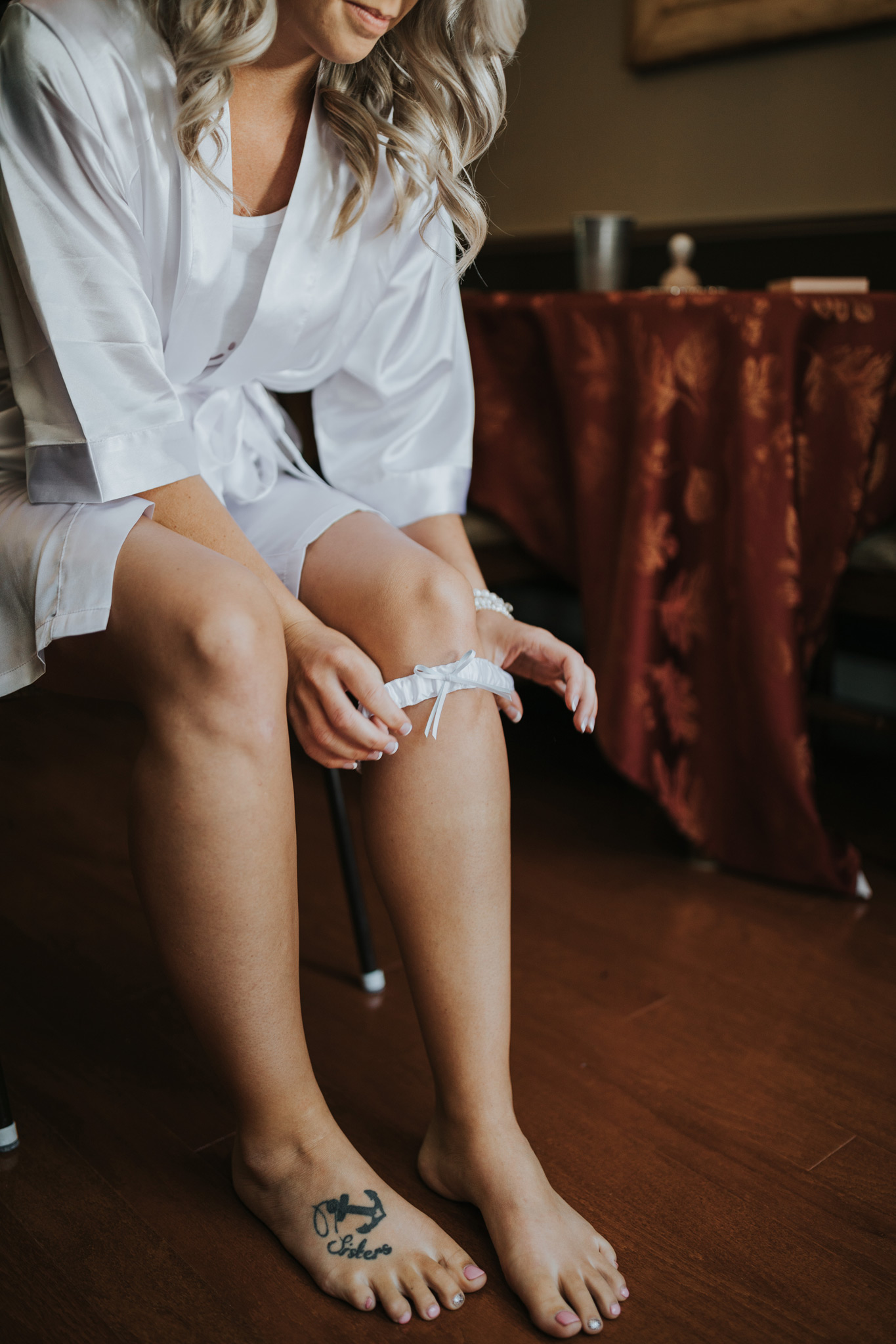 bride in robe putting on her garter