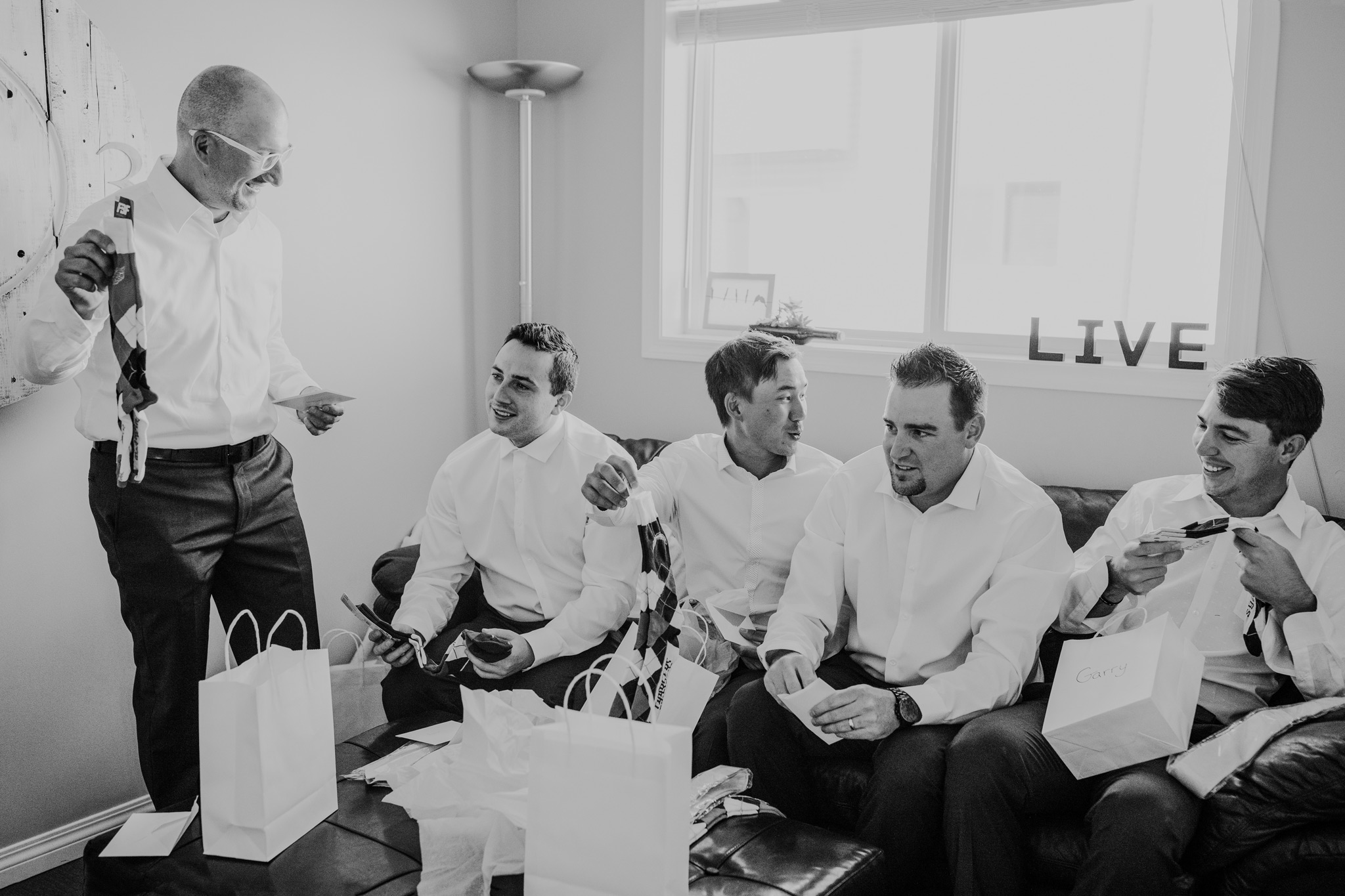 groomsmen opening gift bags with socks