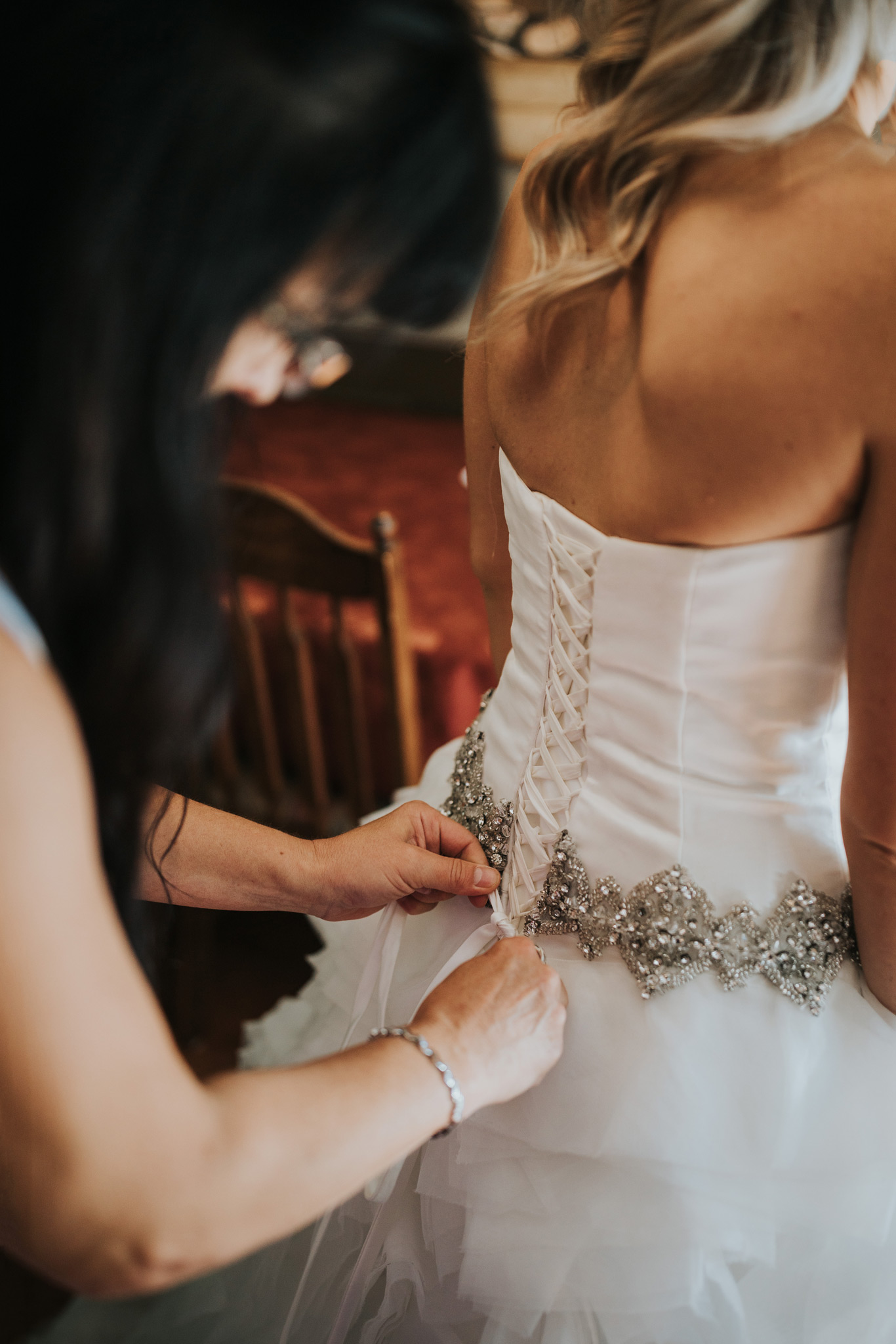brides mother ties up her wedding dress