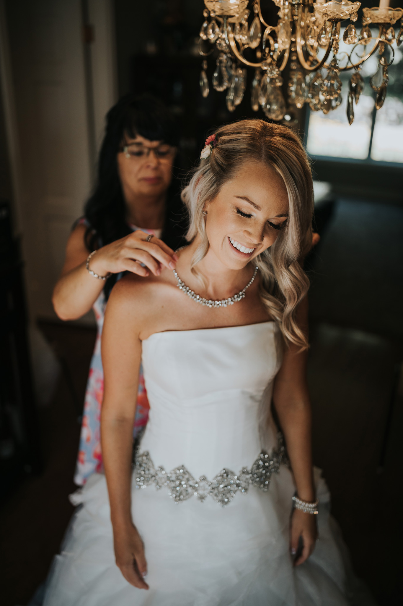 brides mother puts necklace on bride