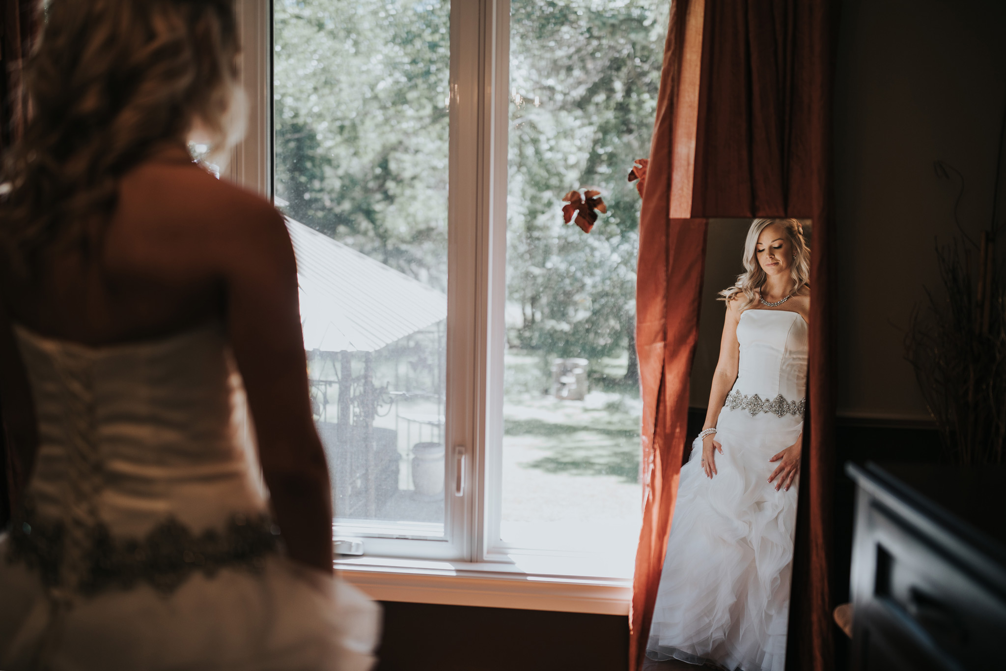 bride standing in mirror seeing herself all put together for the first time