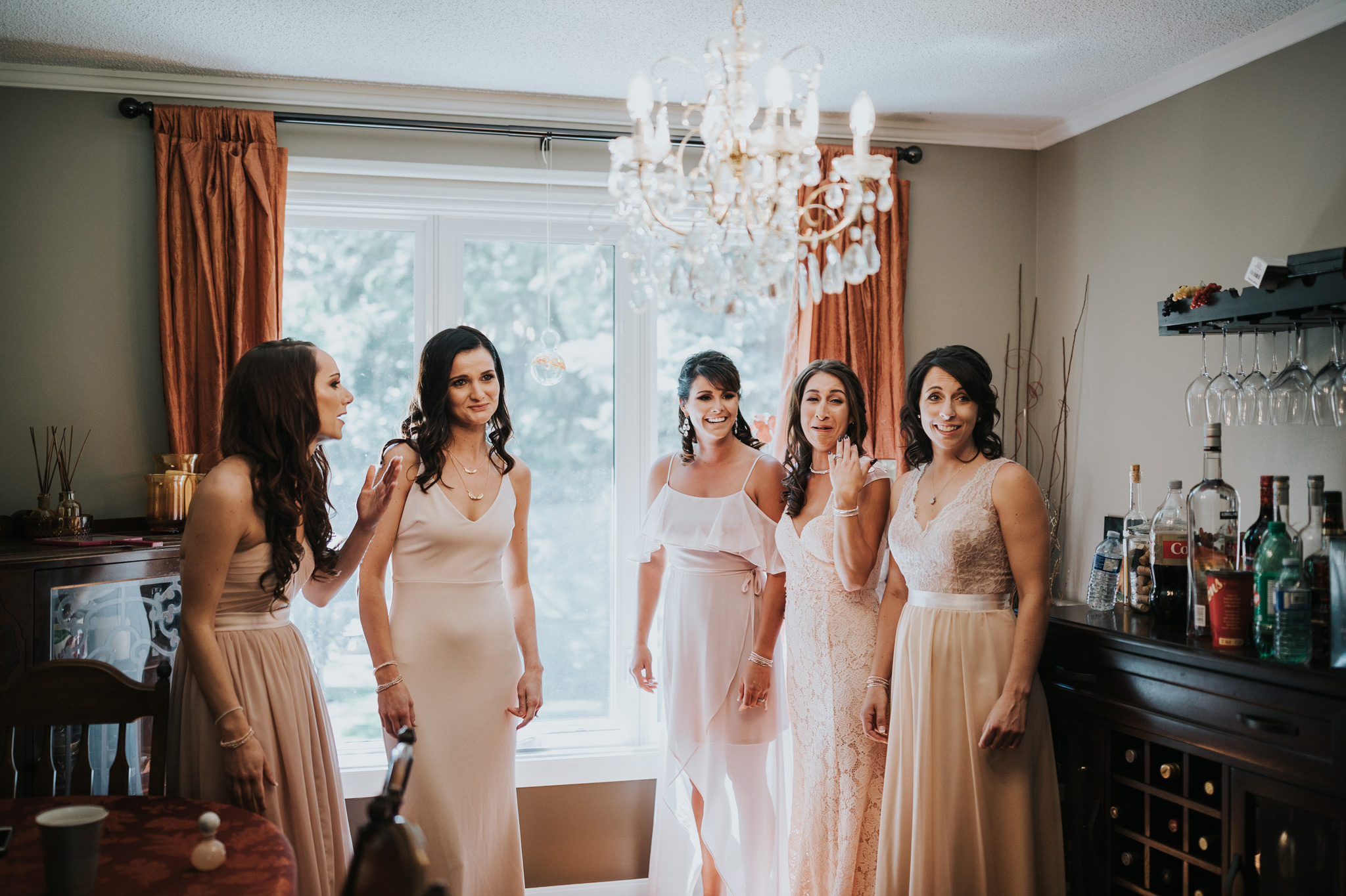 bridesmaids gathered to see the bride for the first time becoming emotional