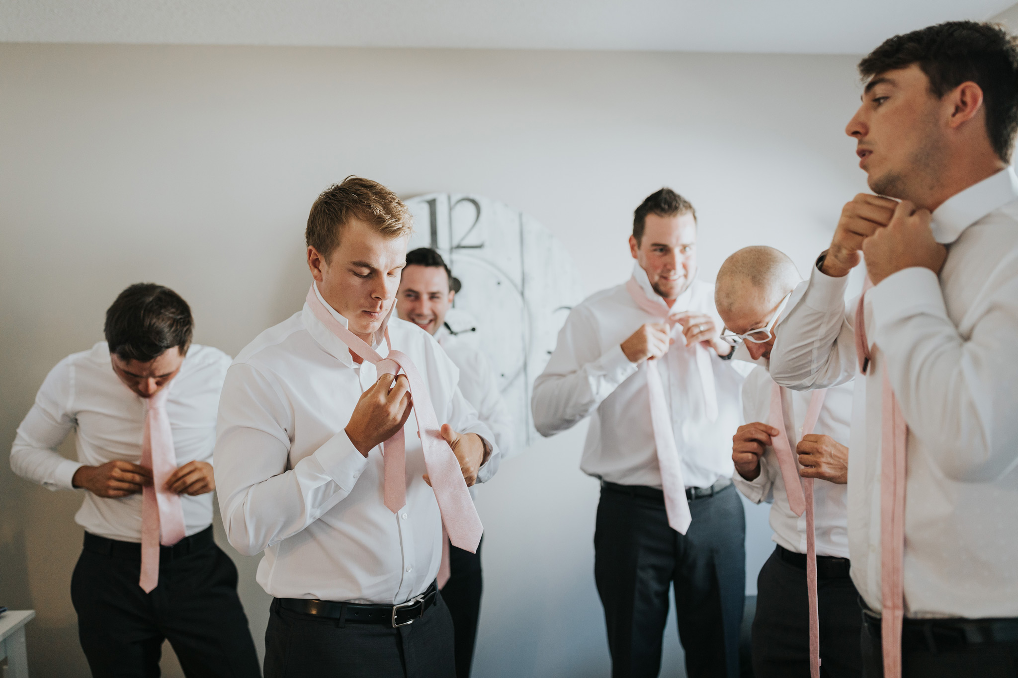 groom with groomsmen tying their wedding ties
