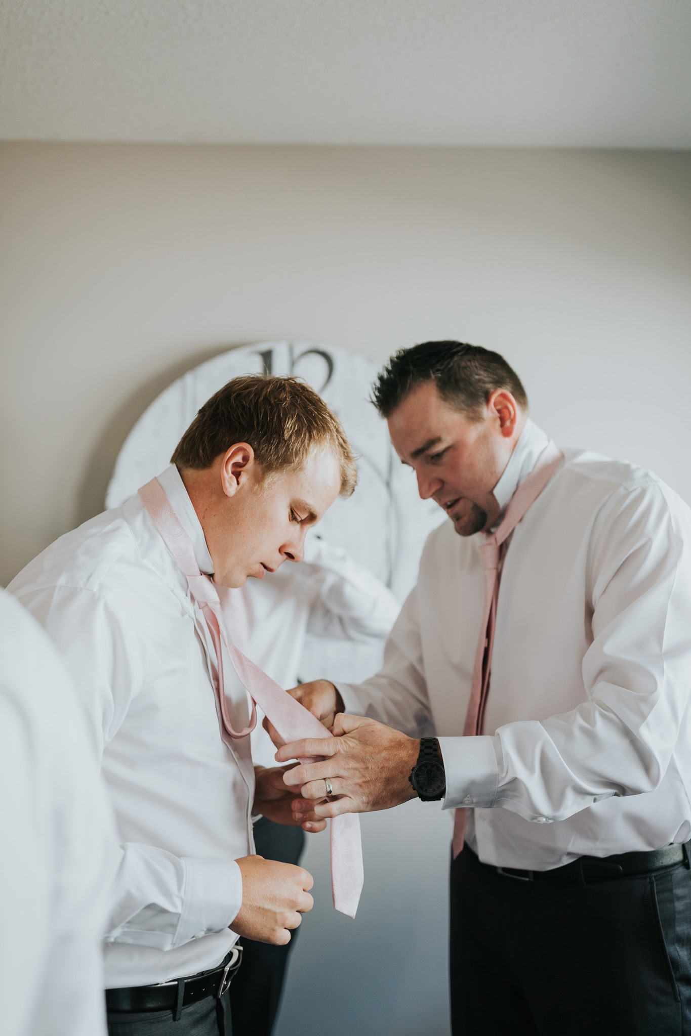 groomsman helping groom tie his wedding tie