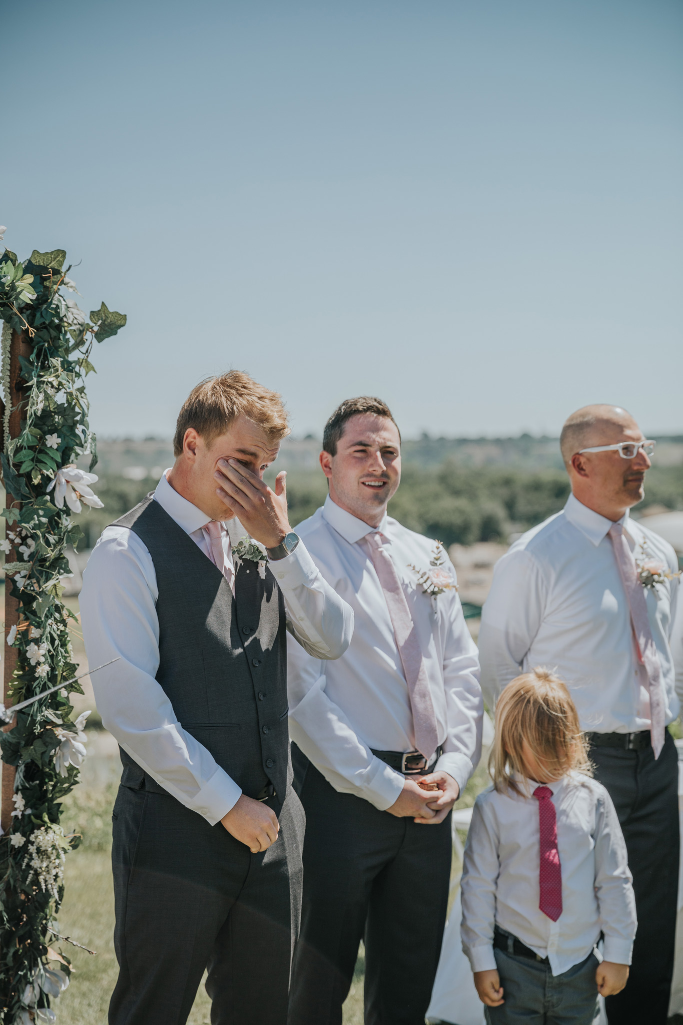 groom wiping away tears as the bride comes down the aisle