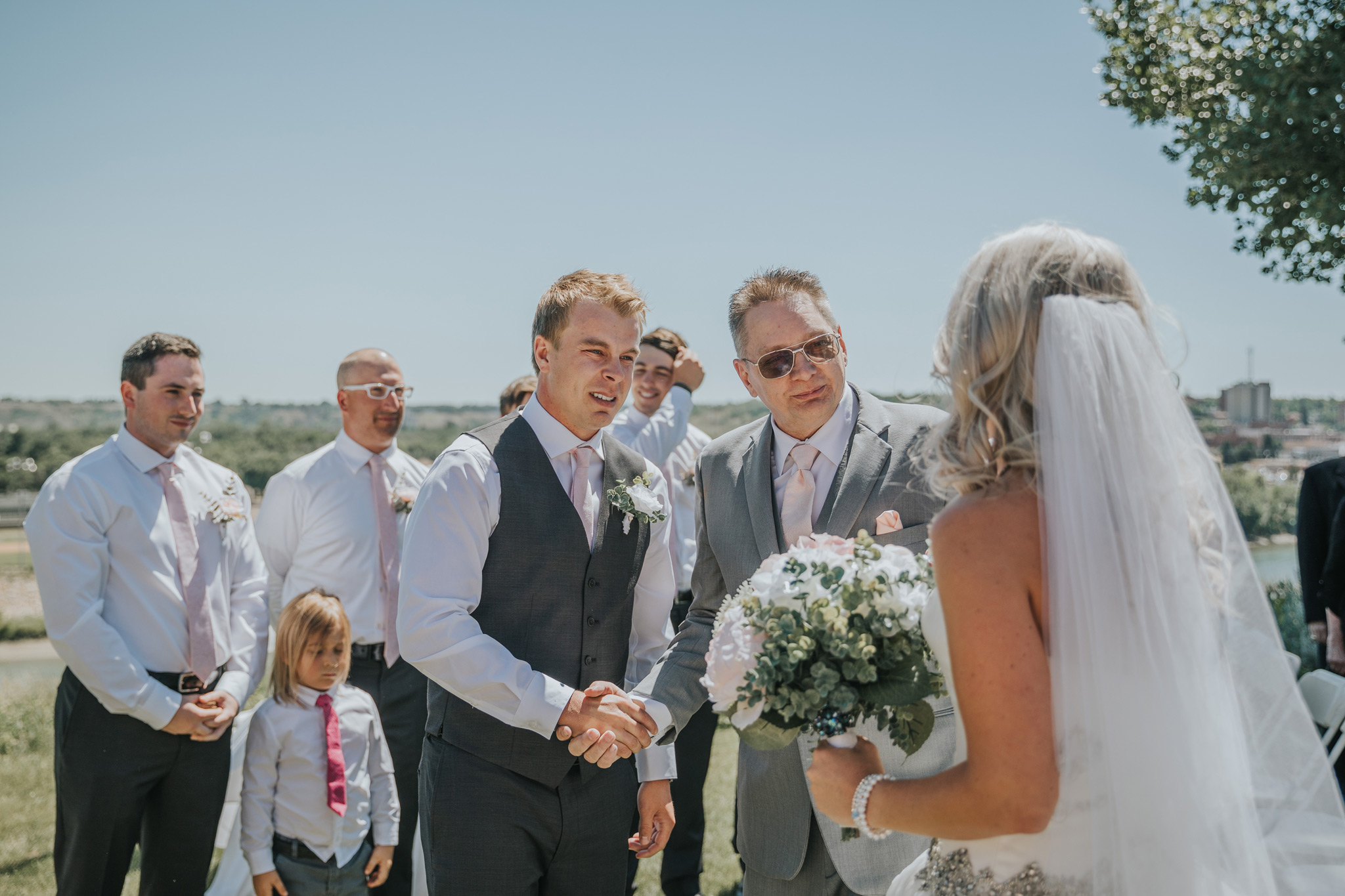 groom shakes father of the brides hand as they both look at the bride