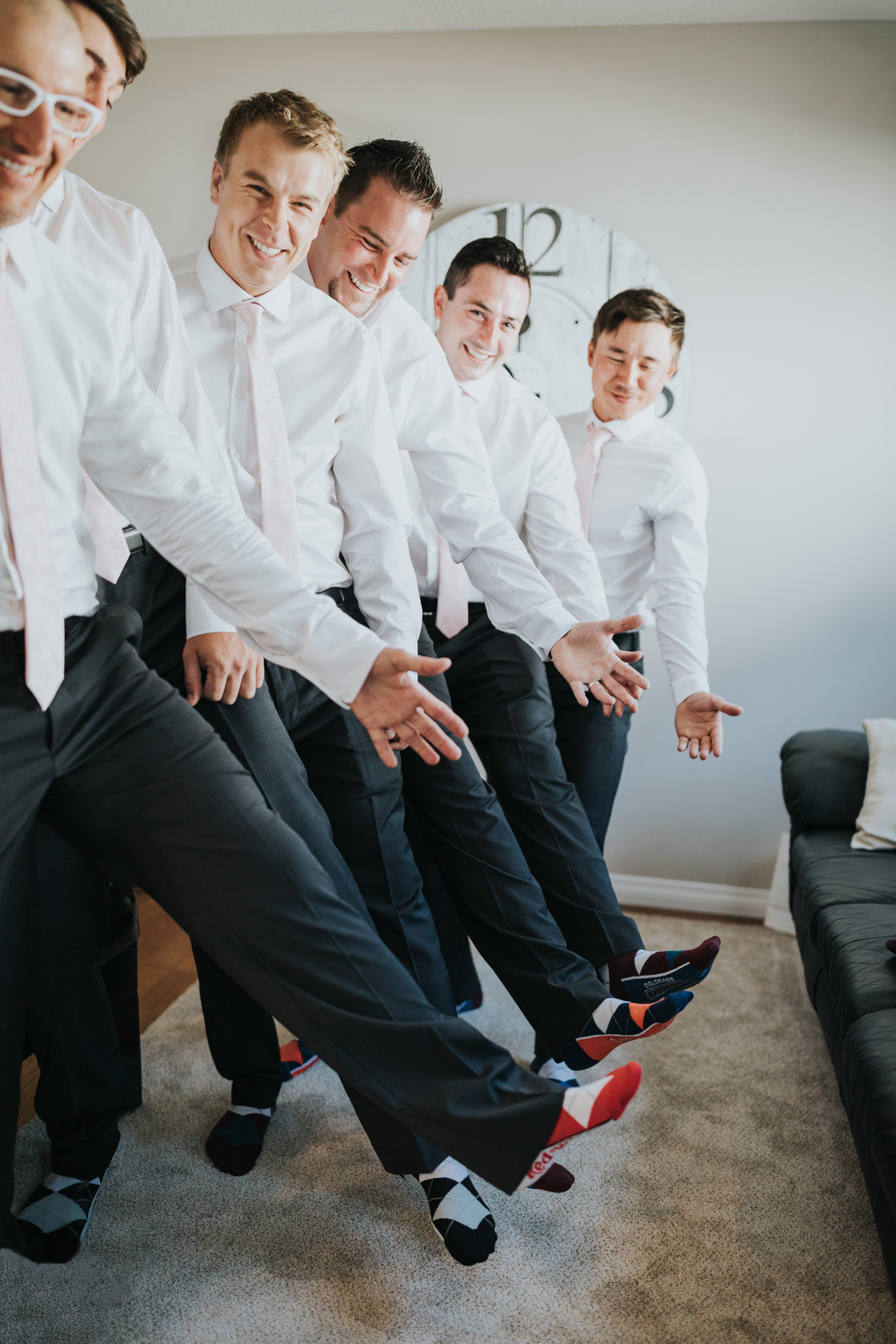 groom with groomsmen showing off their new socks