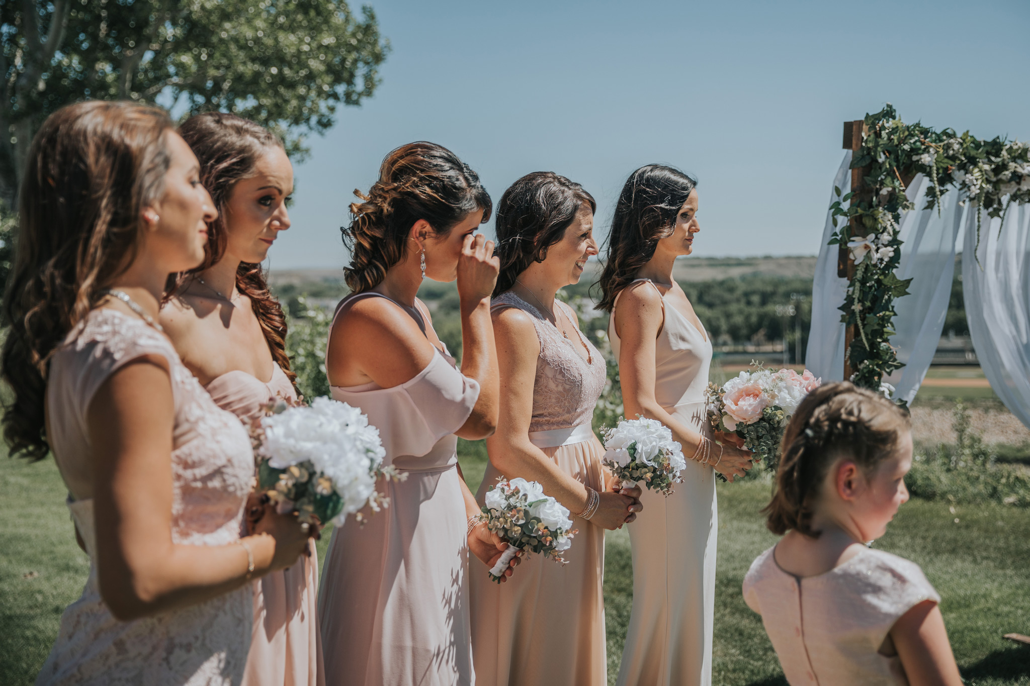 bridesmaids watching the ceremony as one wipes away a tear
