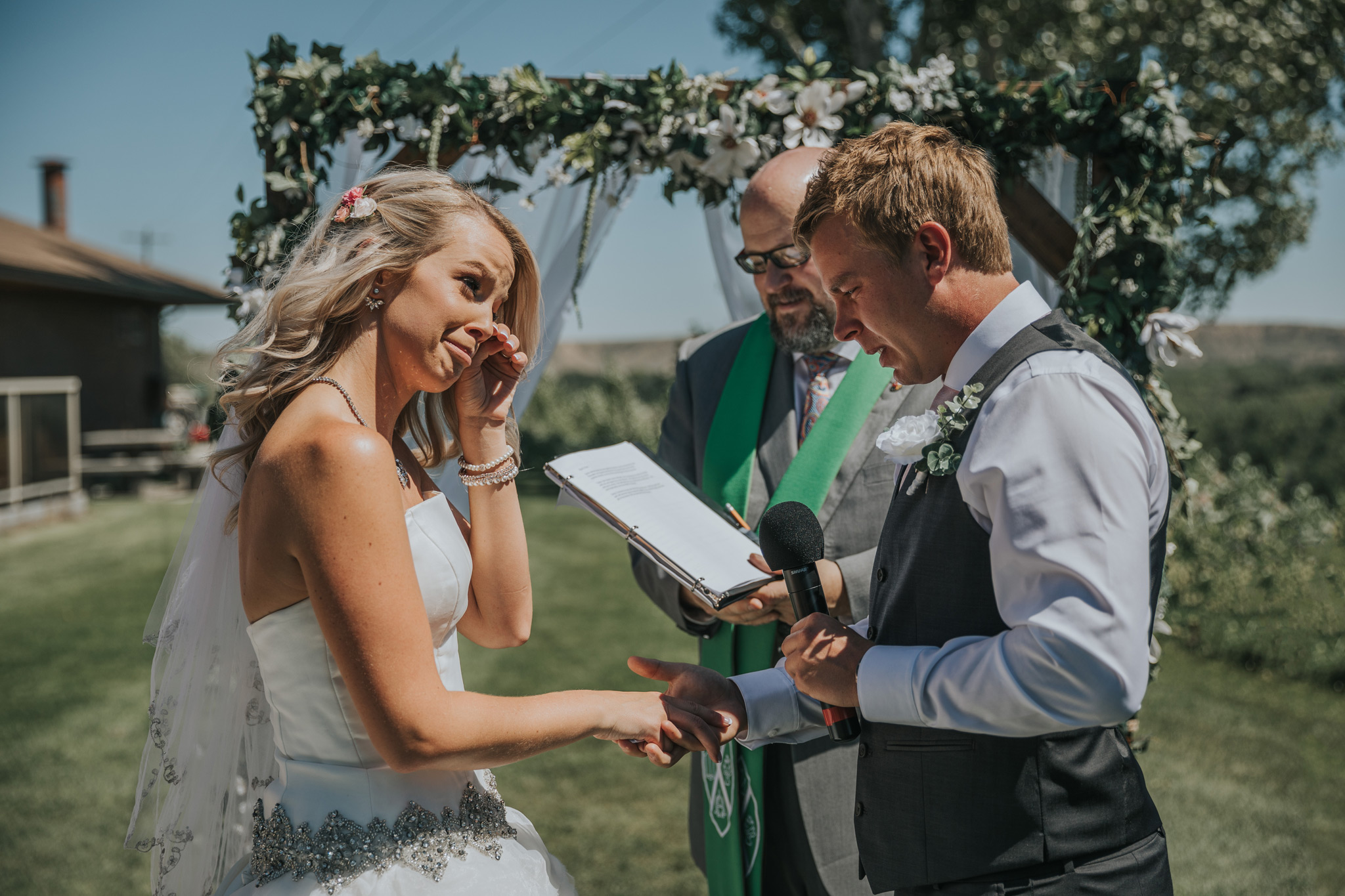 bride wipes away tears exchanging vows