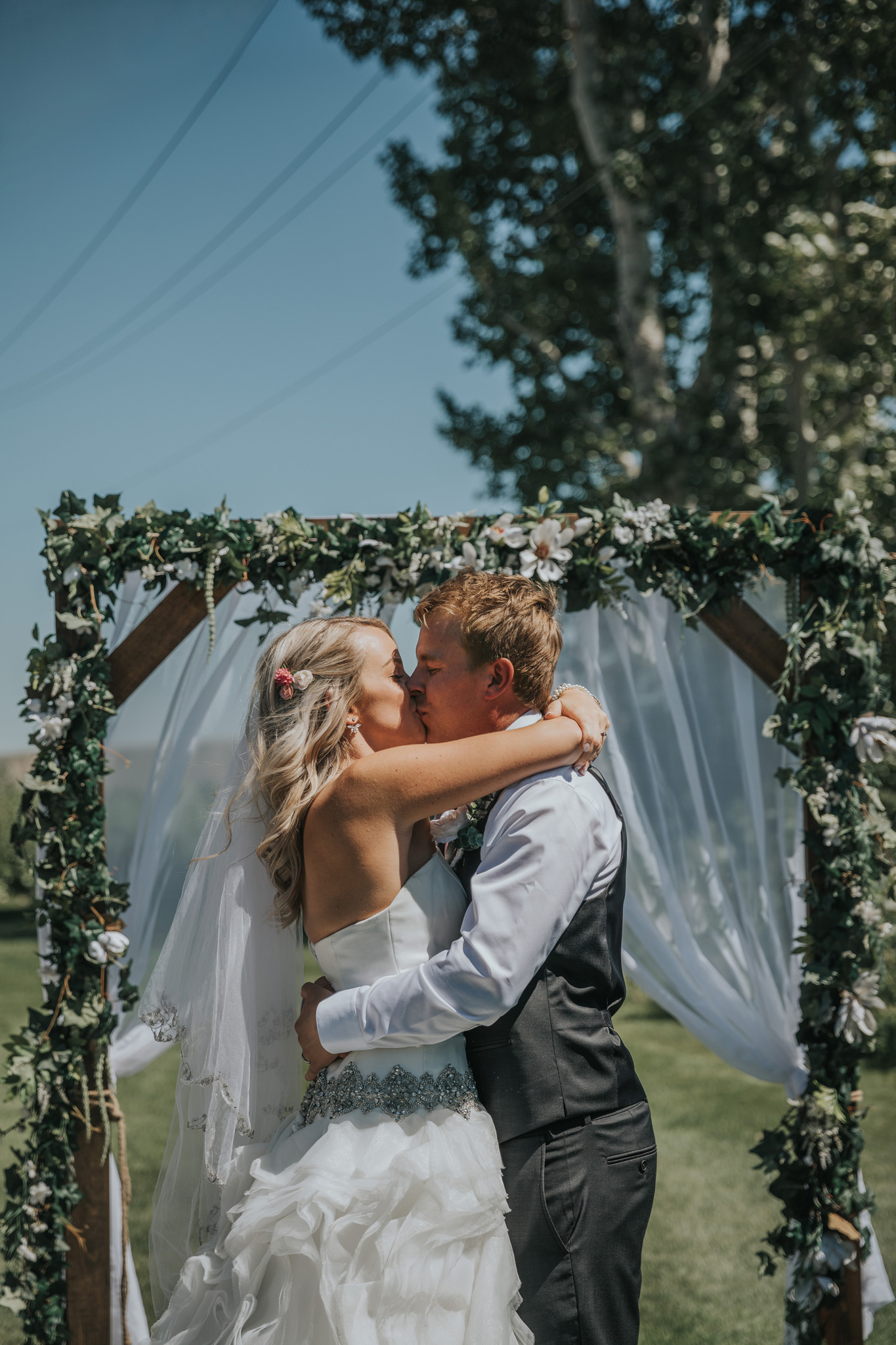 bride and groom kiss under wedding arch medicine hat gold and country club wedding