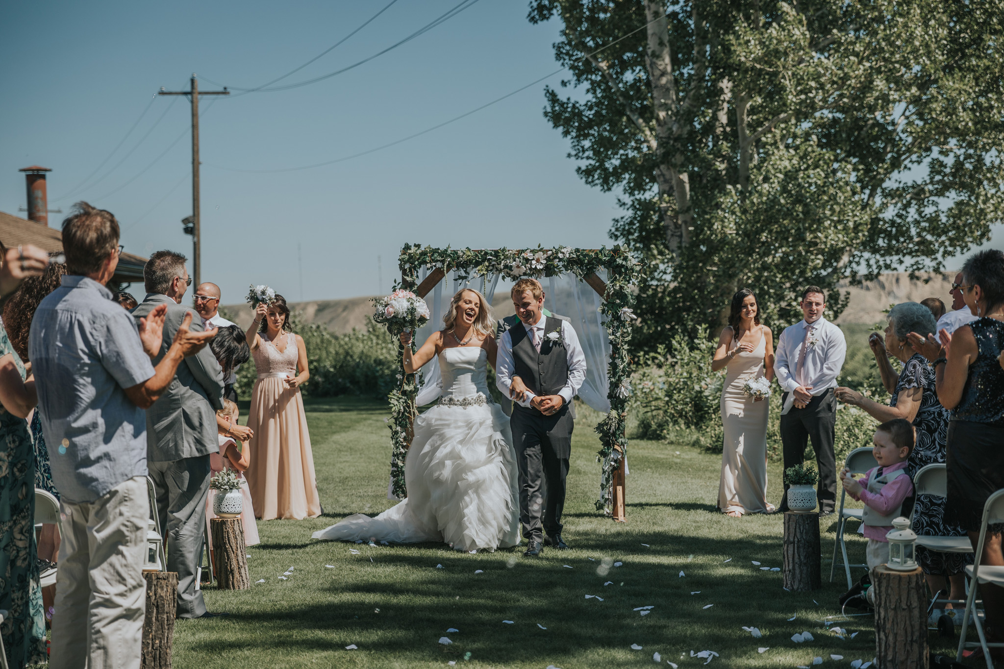 bride and groom walk down the aisle celebrating medicine hat golf and country club wedding