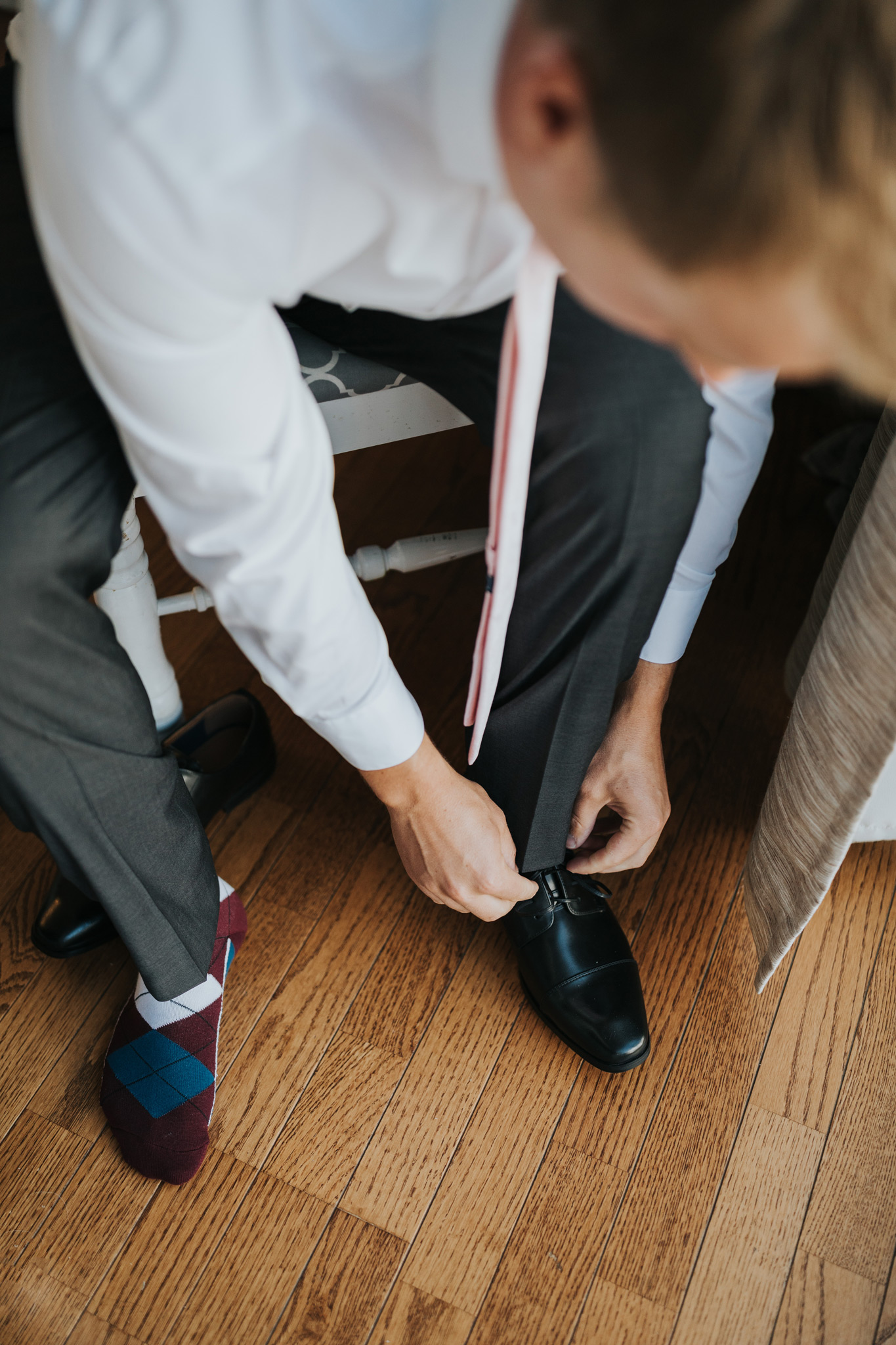 groom putting on shoes for wedding