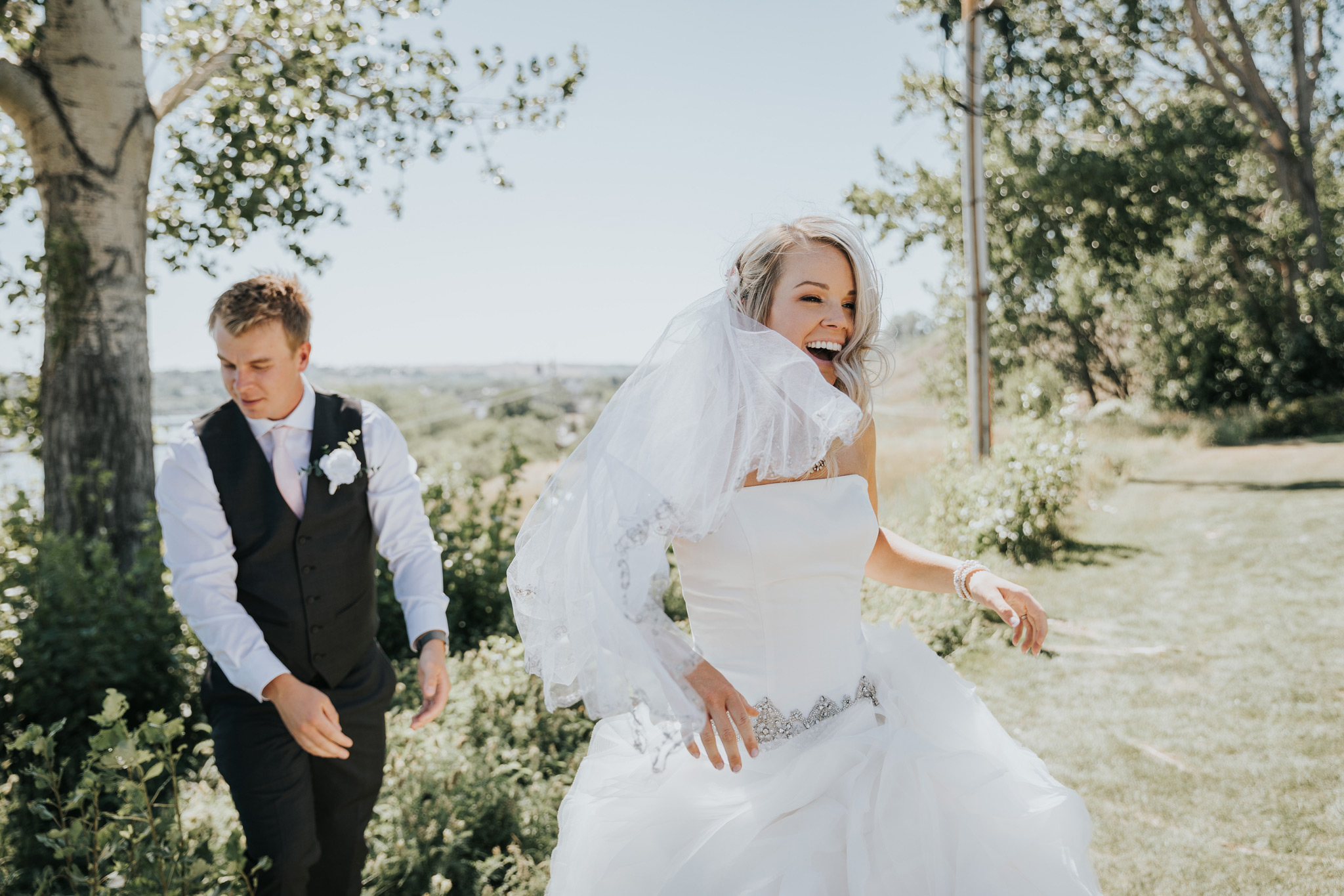bride laughs as the wind blows her veil