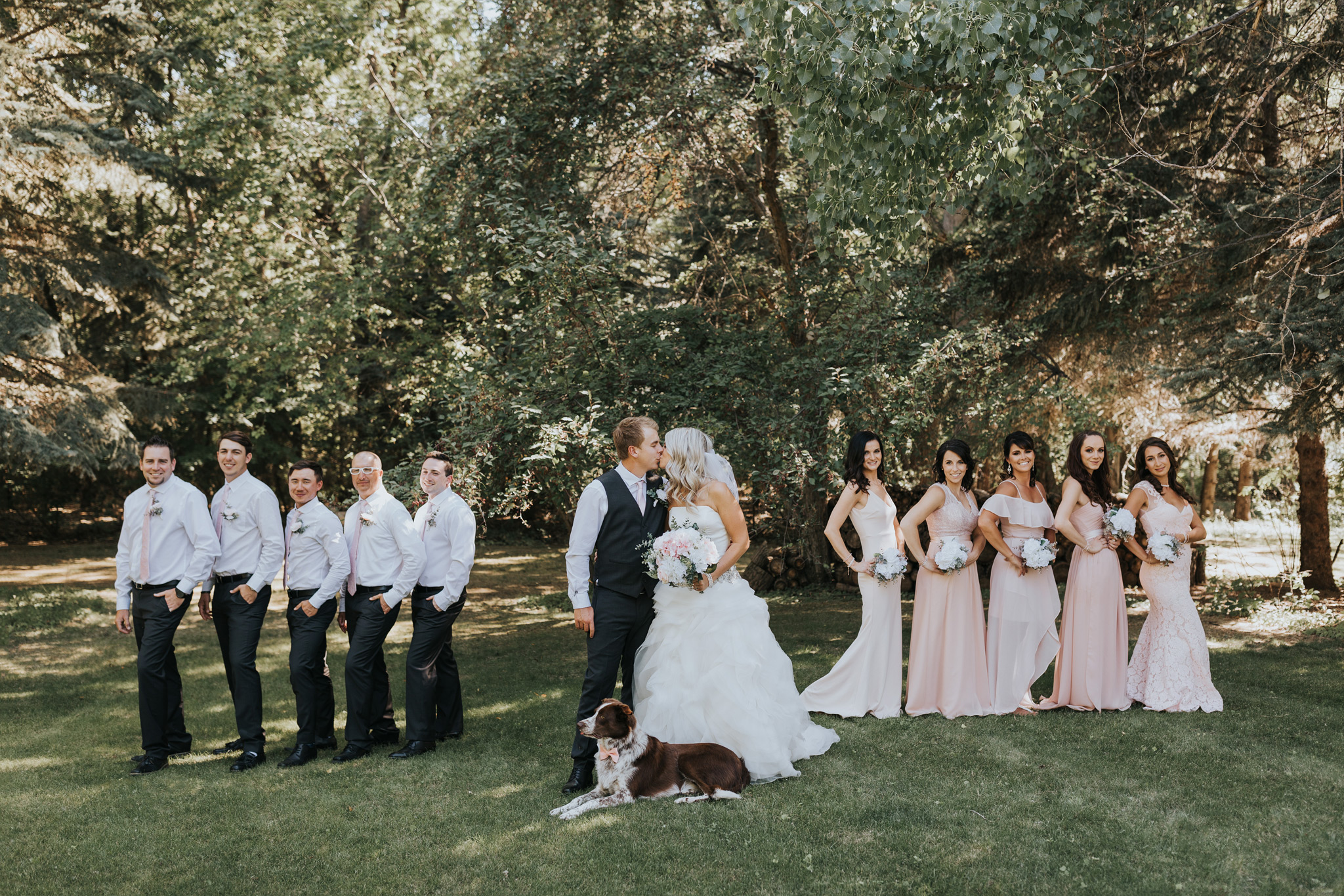bride and groom kiss with bridal party behind them
