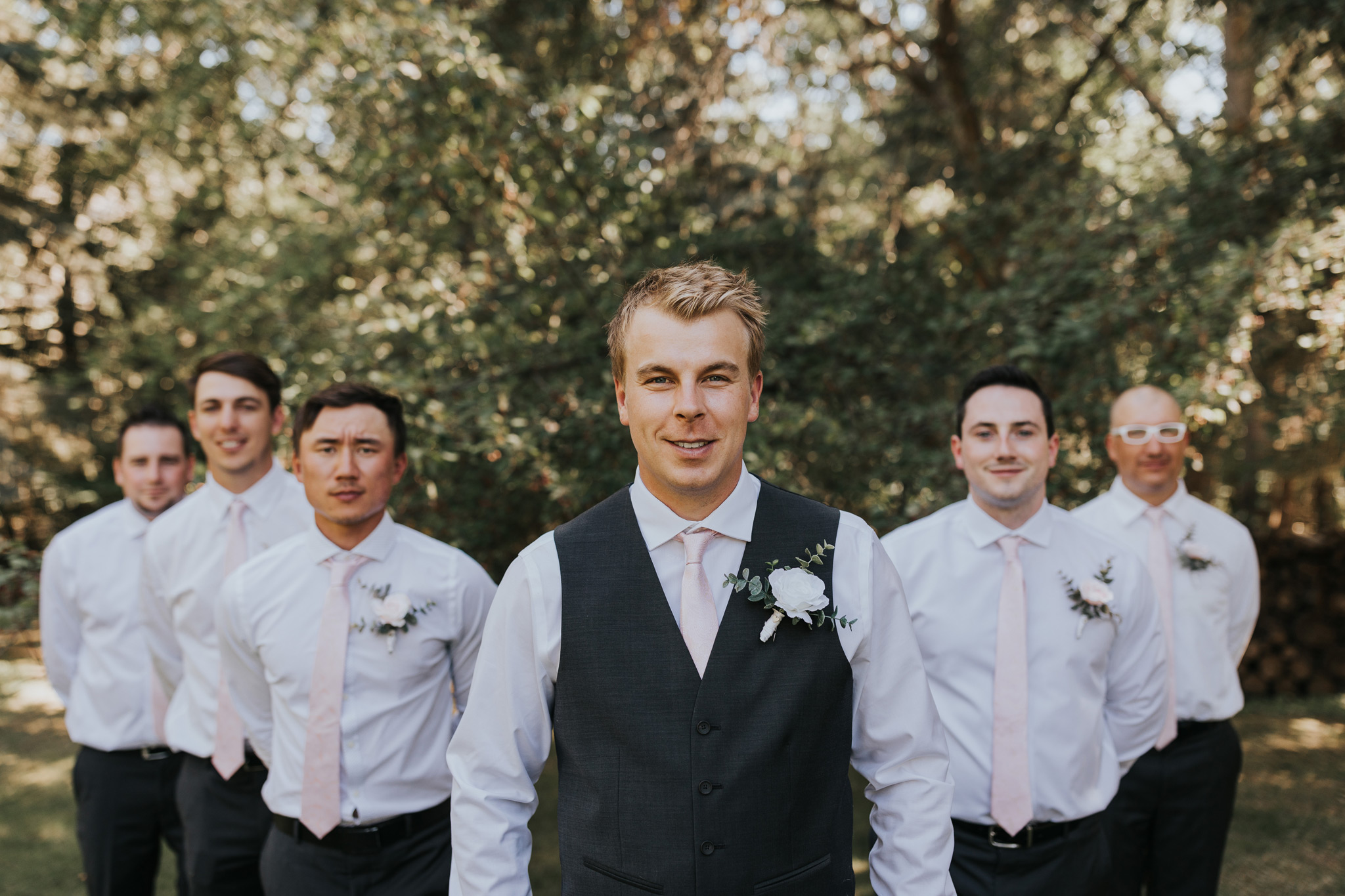 groom stands with groomsmen behind him