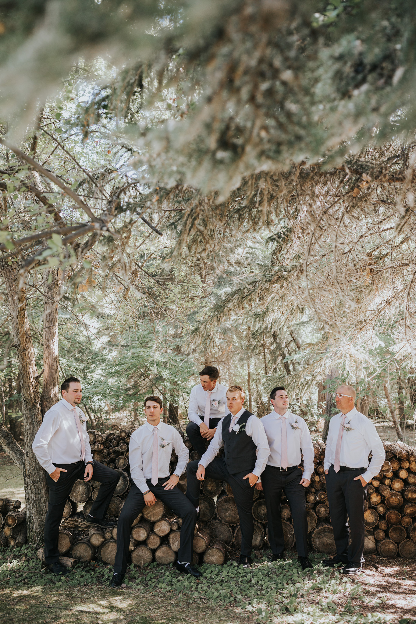 groomsmen serious pose by a log pile