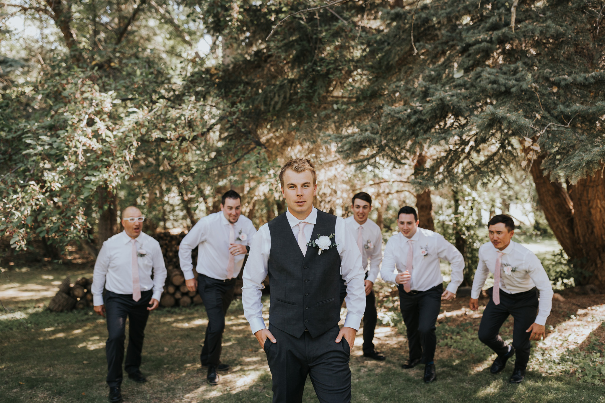groom poses as groomsmen run up behind him