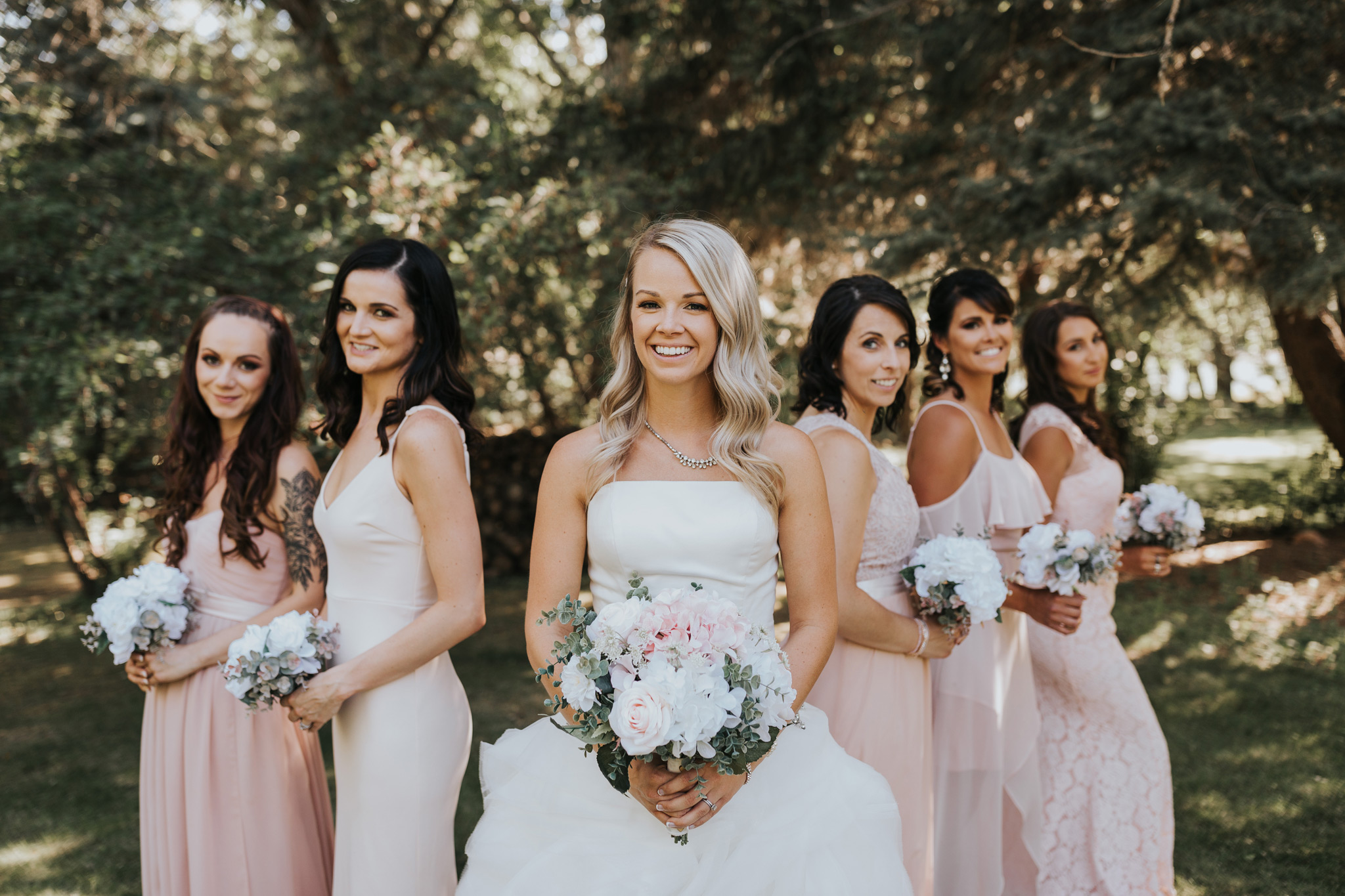 bride stands with bridesmaids behind her