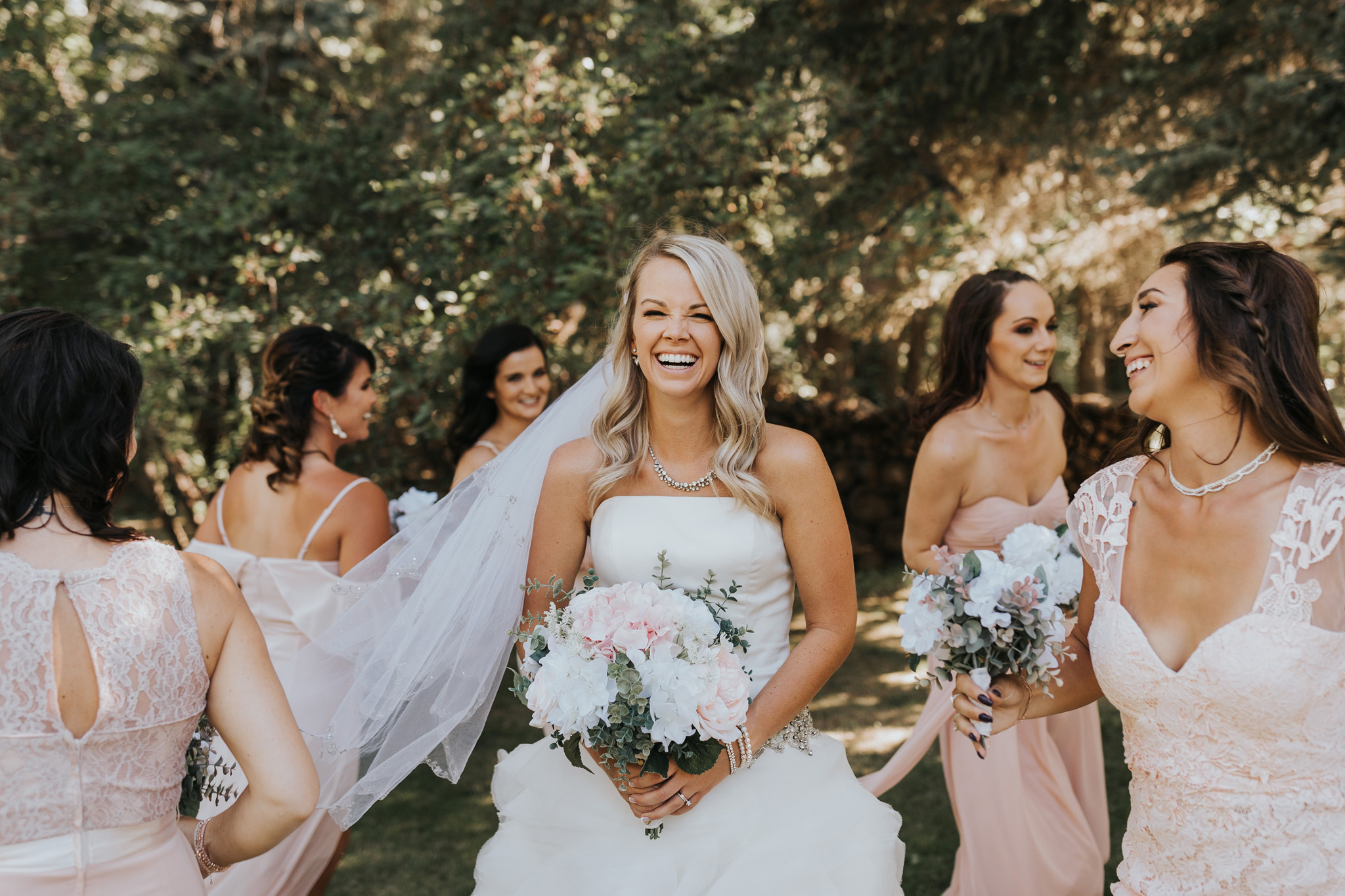 bride stands while bridesmaids run around her