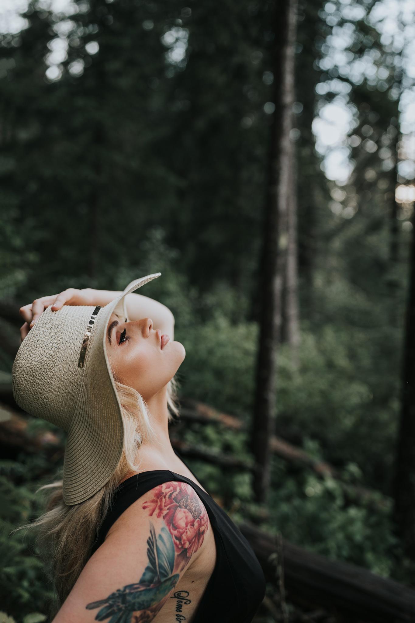 woman leans back holding hat on head reesor lake alberta