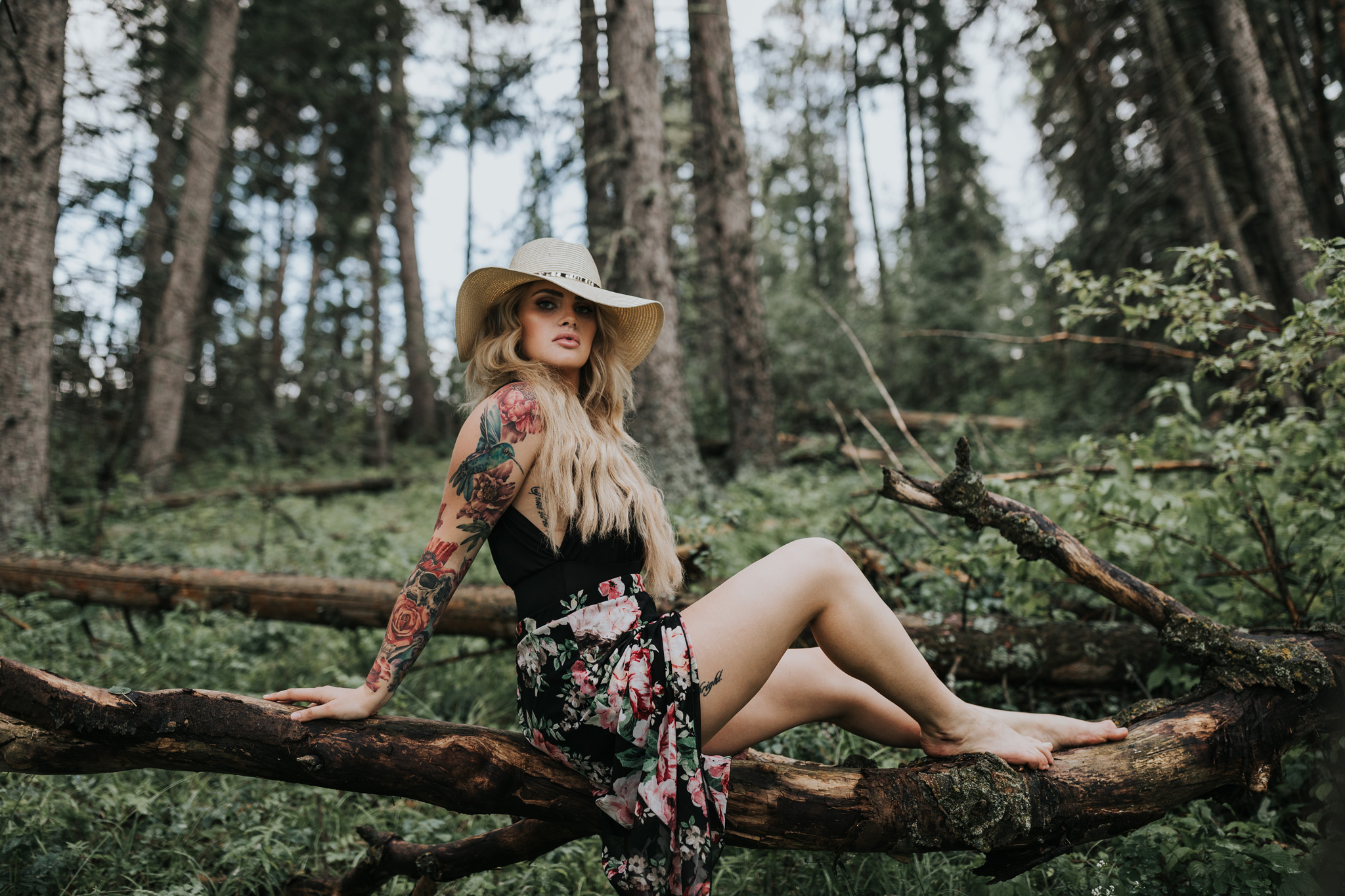 woman sitting on suspended tree log wearing hat cypress hills